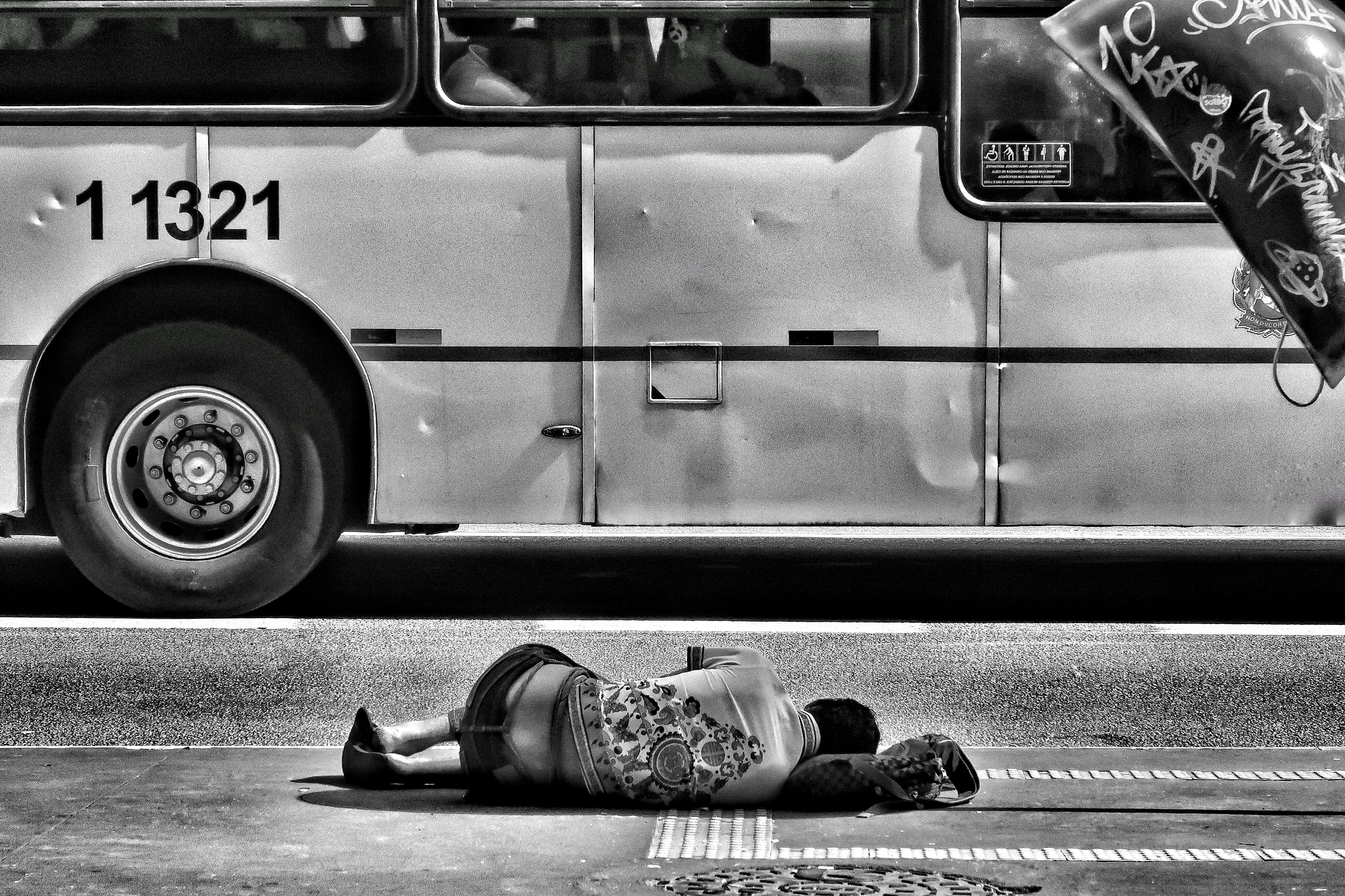 grayscale photography of person laying on ground near bus