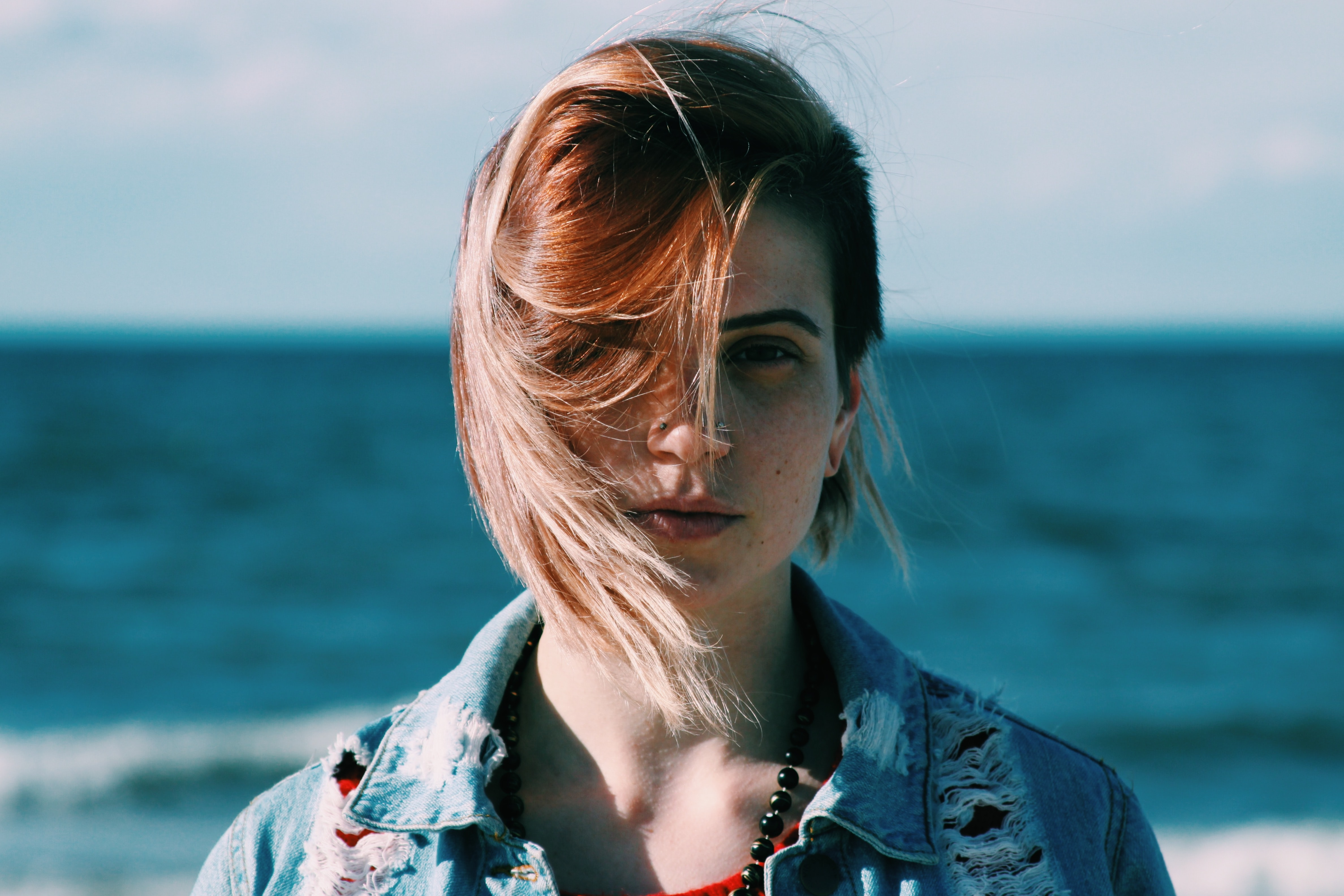 woman in brown denim jacket standing near on beach during daytime shallow focus photography