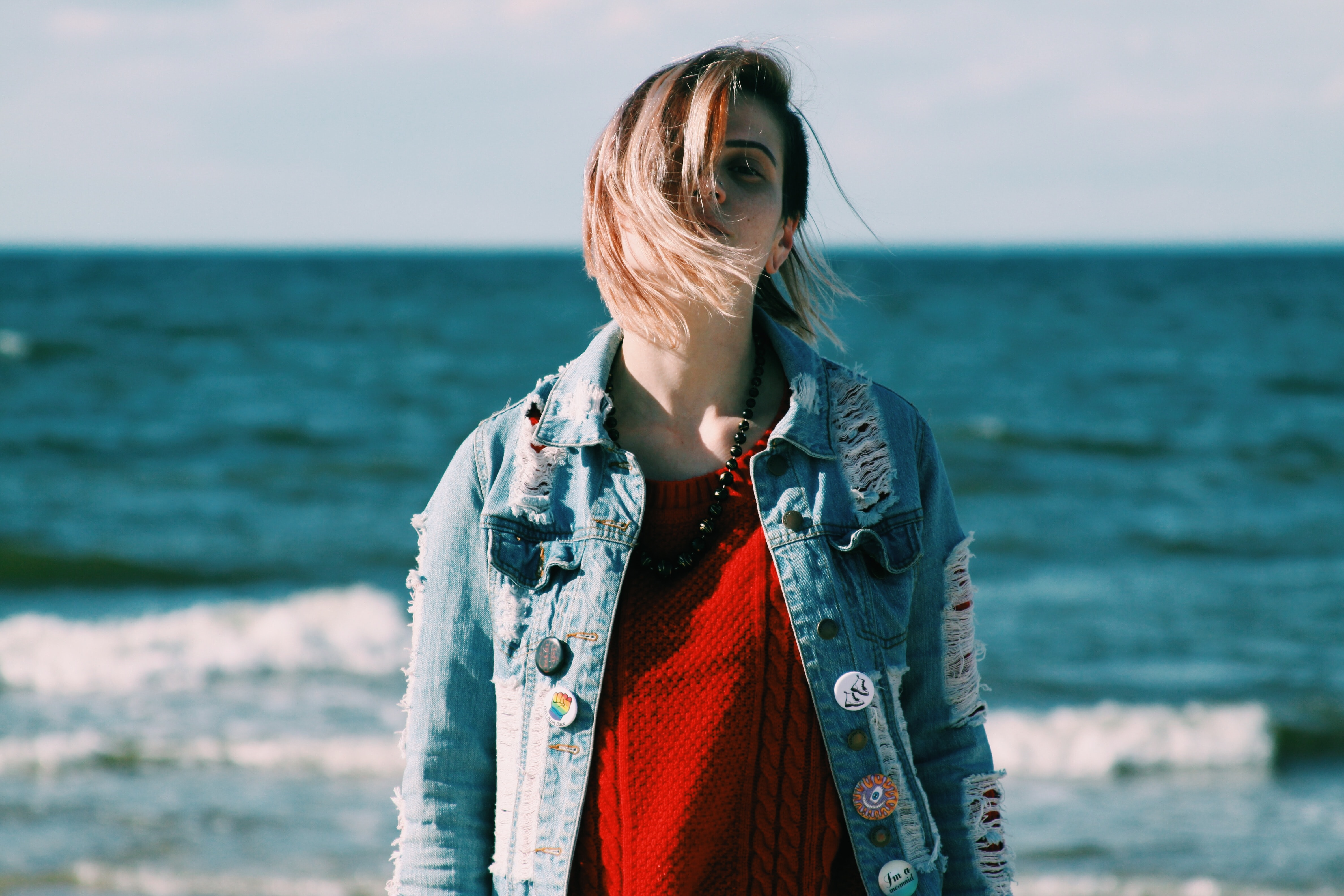woman wearing blue denim jacket standing near body of water