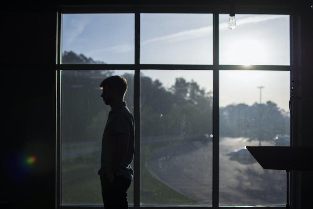 silhouette photo of man standing near mirror