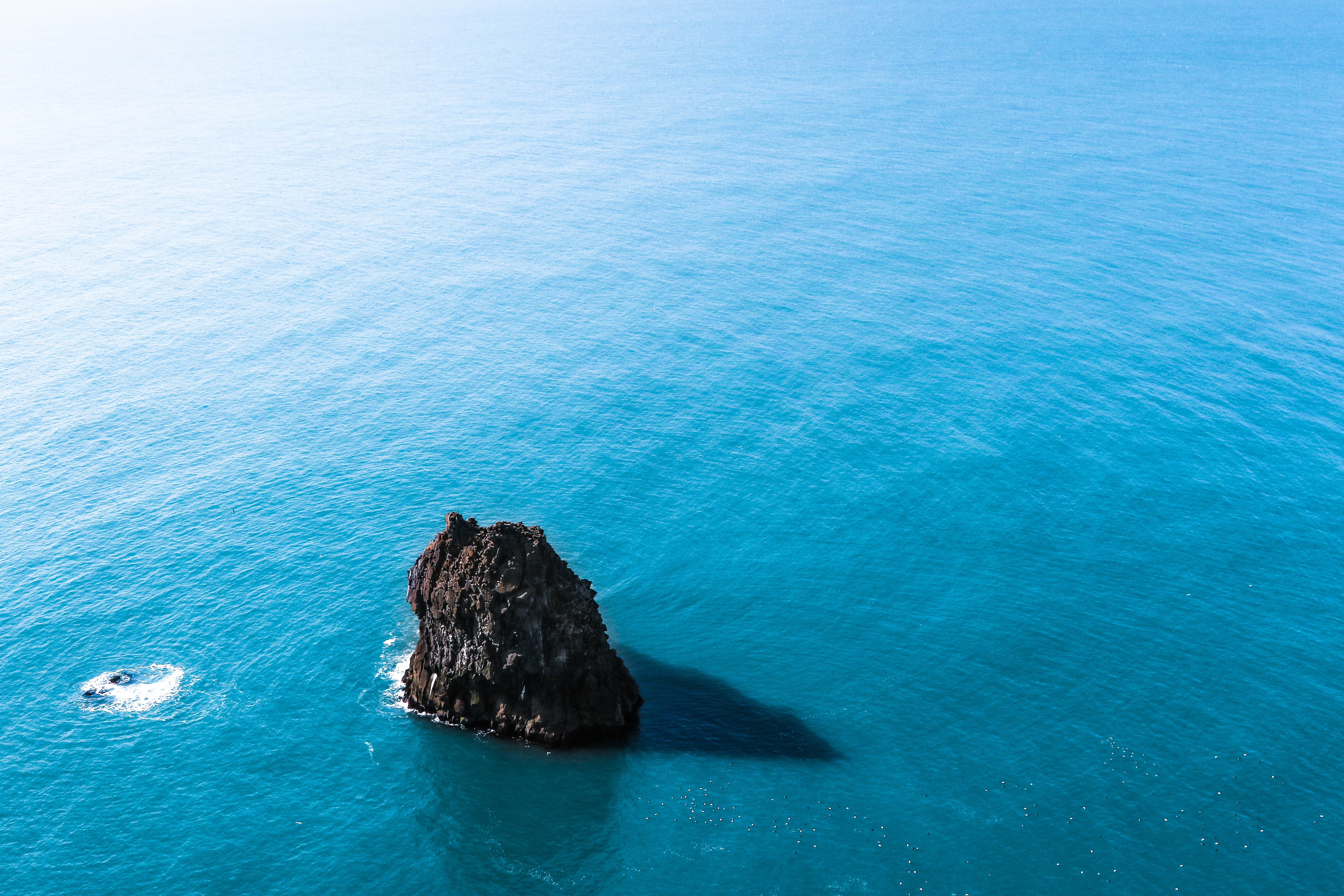 A large black rock in the middle of the bright blue sea