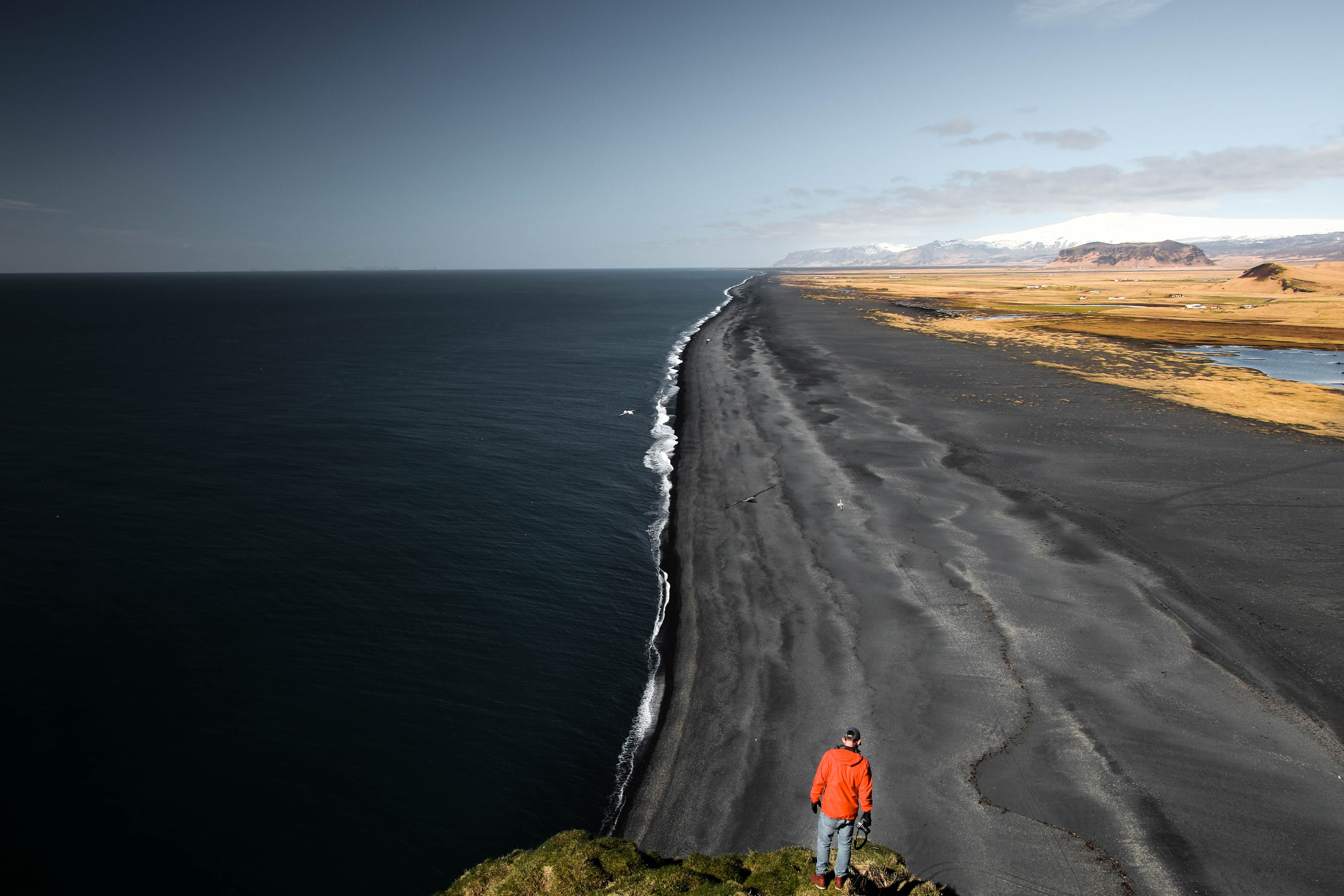Man standing on the rock looking at the black sand beach in Vik