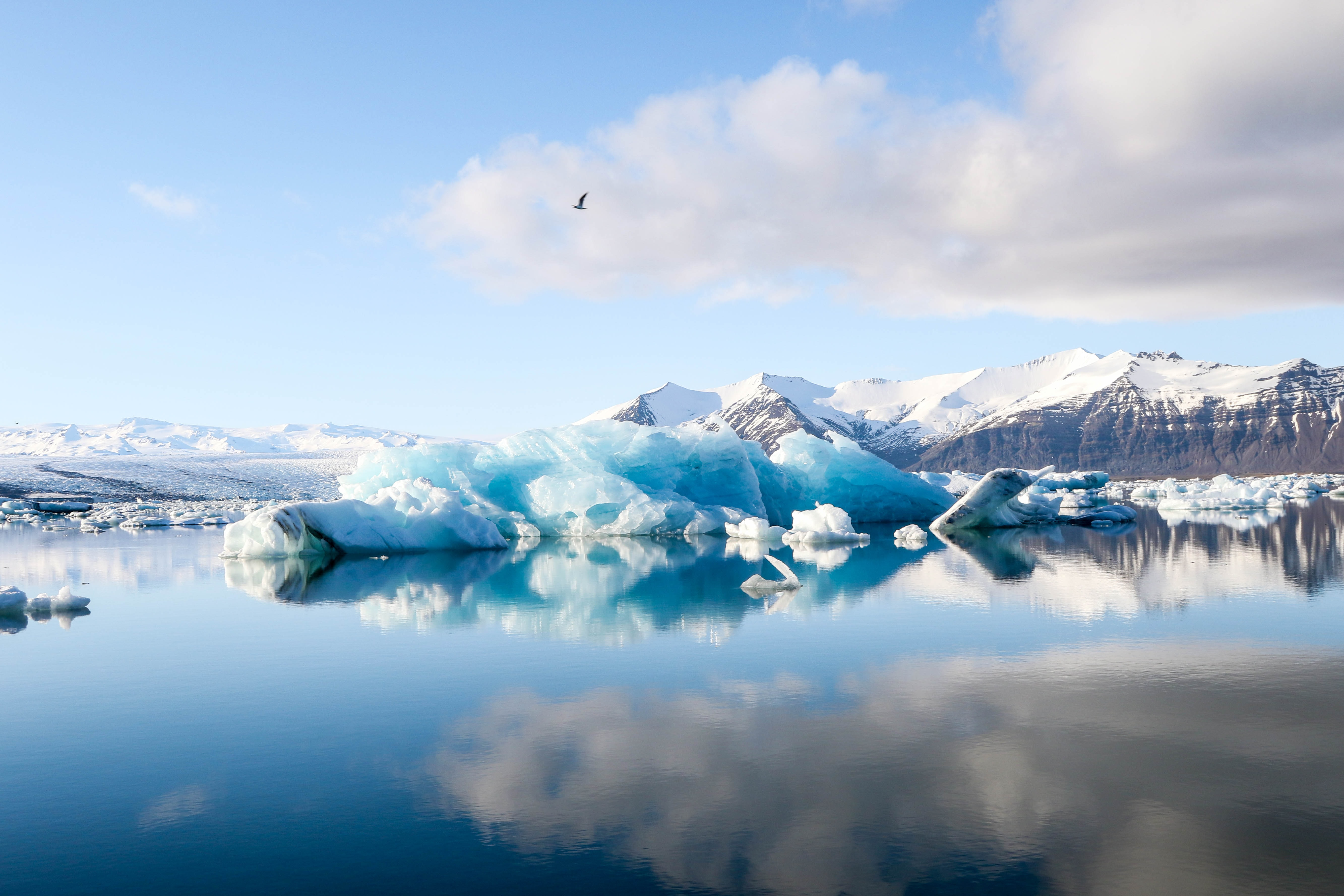 A landscape view of an iceberg and its reflection in the water clear blue water.