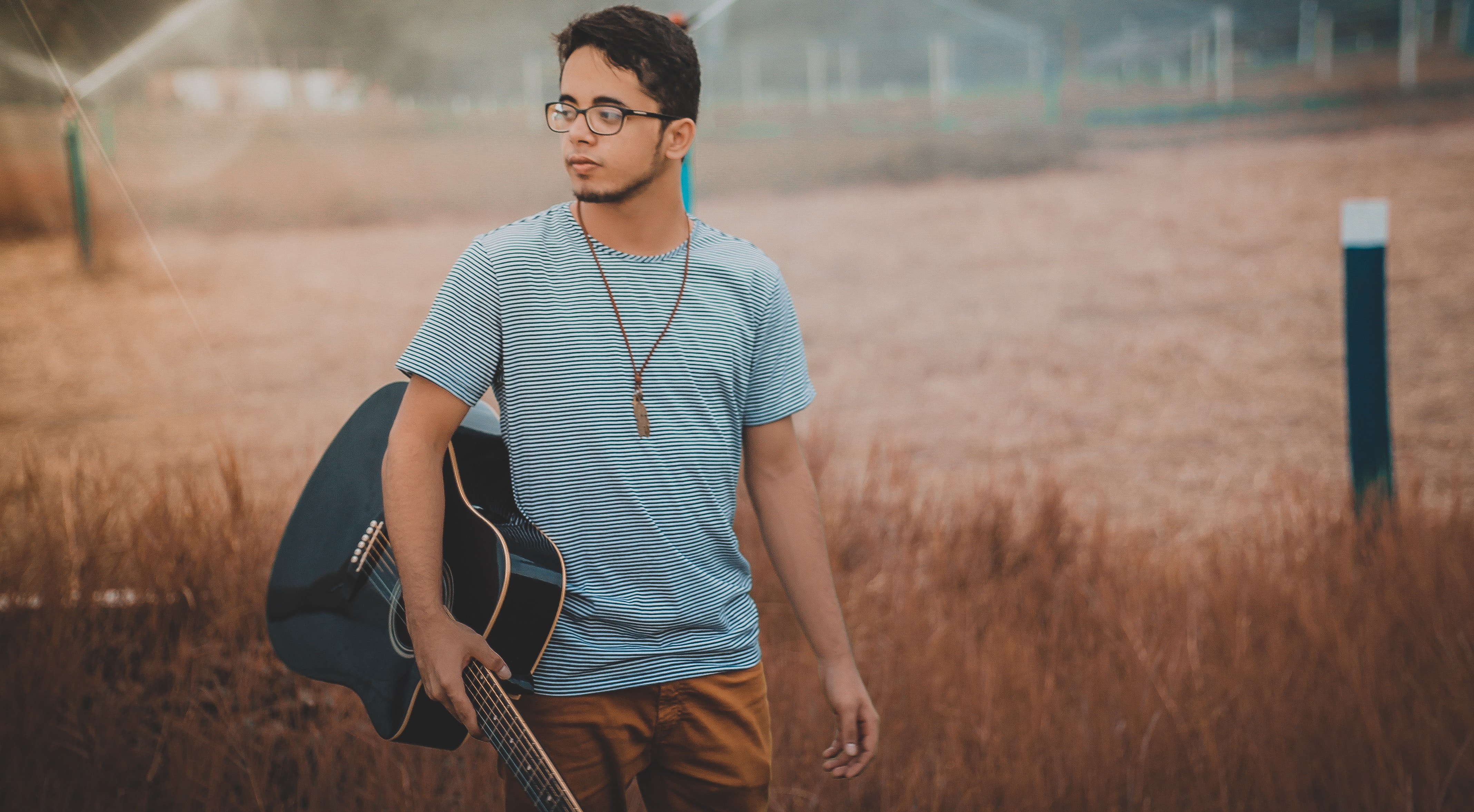 A man in a striped shirt with glasses is holding a guitar in a field.