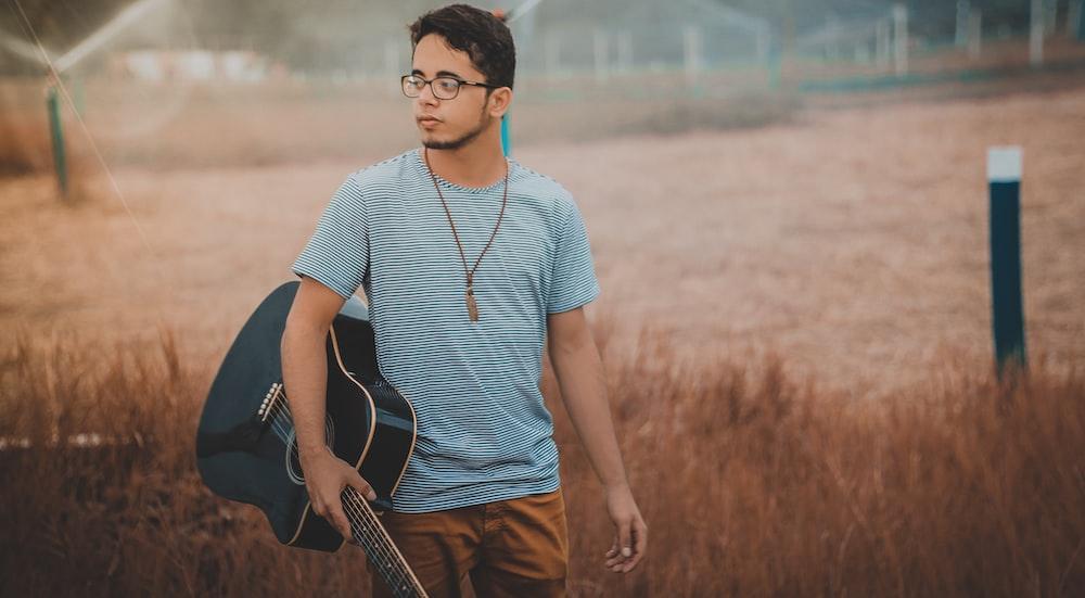 man holding cutwaya acoustic guitar