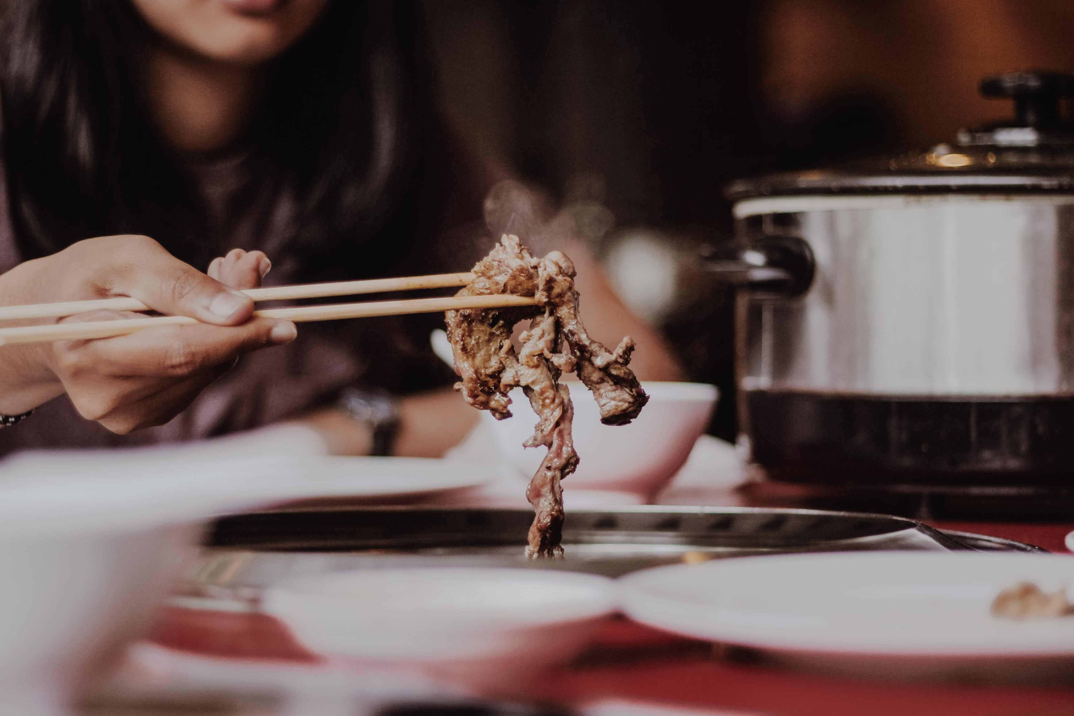 A close-up of women taking strips of steaming meat with chopsticks next to a cooker.