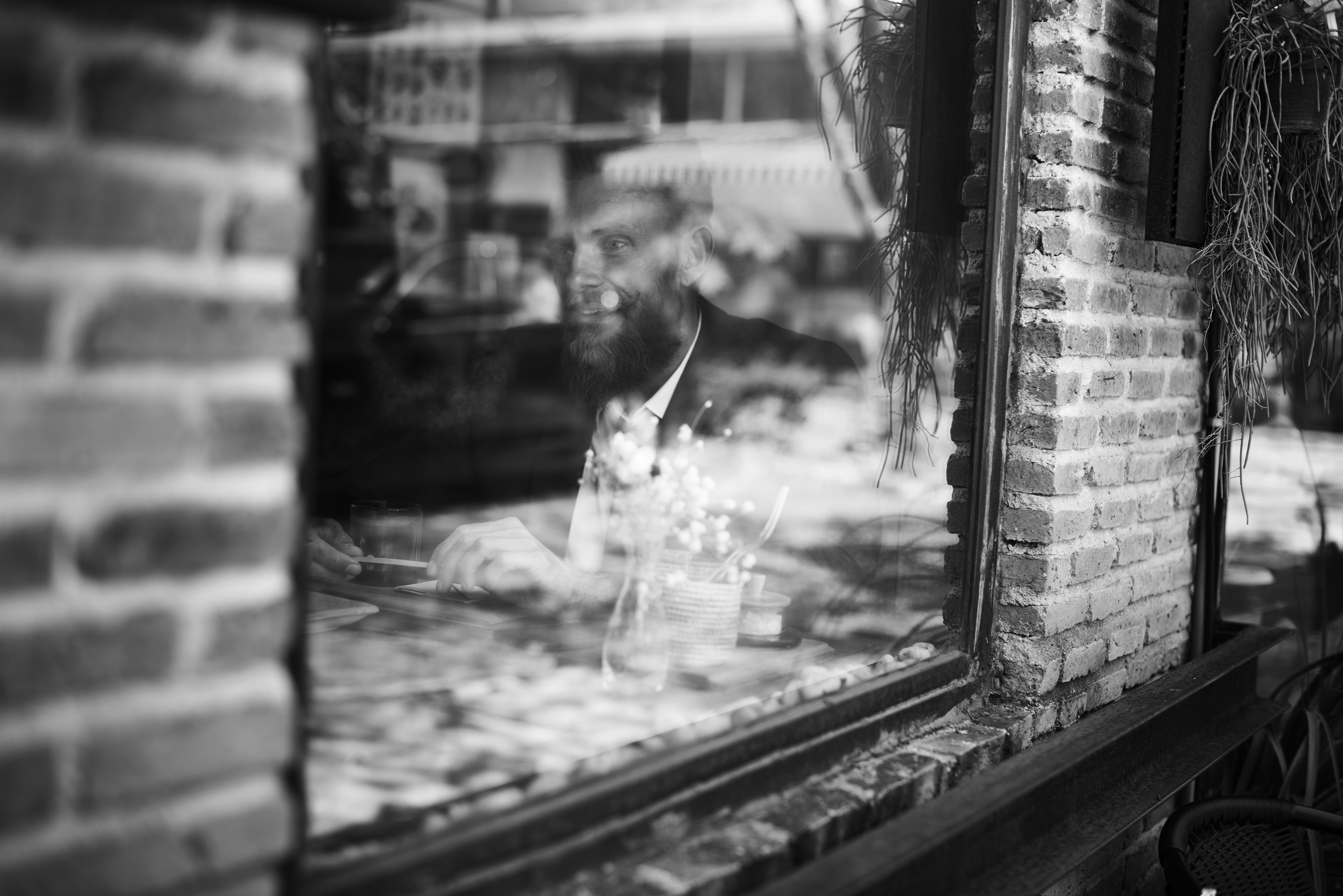 man dining near glass window with brick wall black and white photography