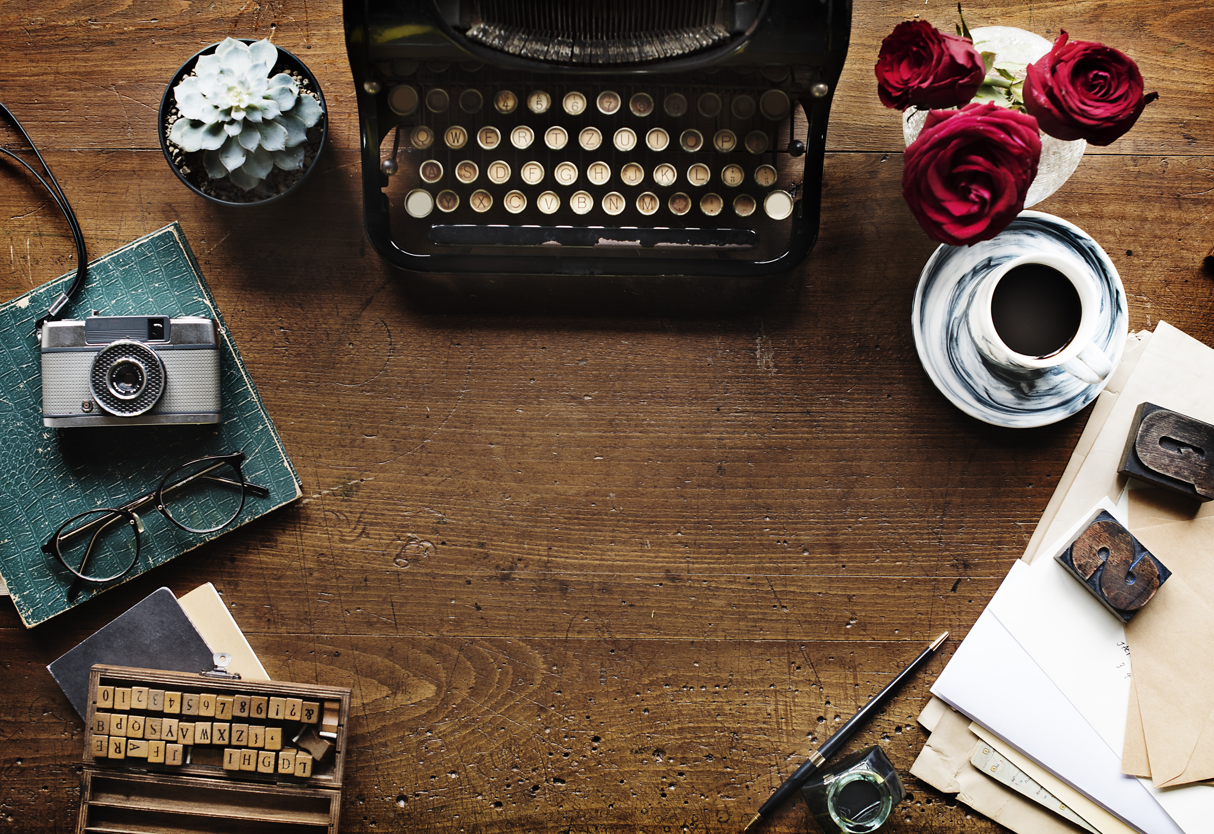 A flatlay with a vintage typewriter, pieces of wooden type, a cup of coffee and red roses