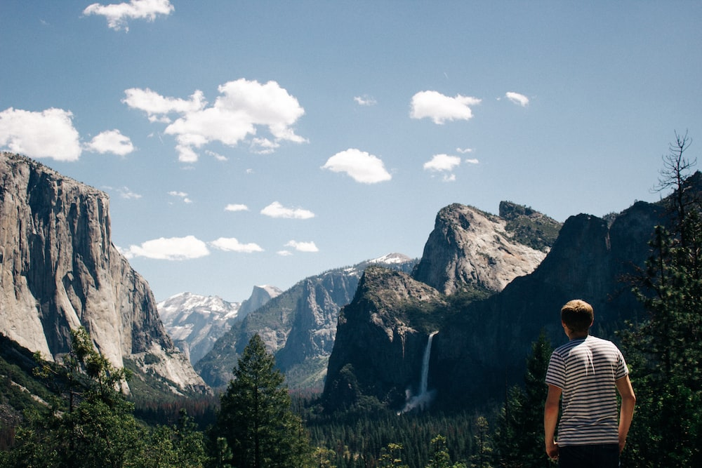 man standing next to mountains with waterfalls and trees