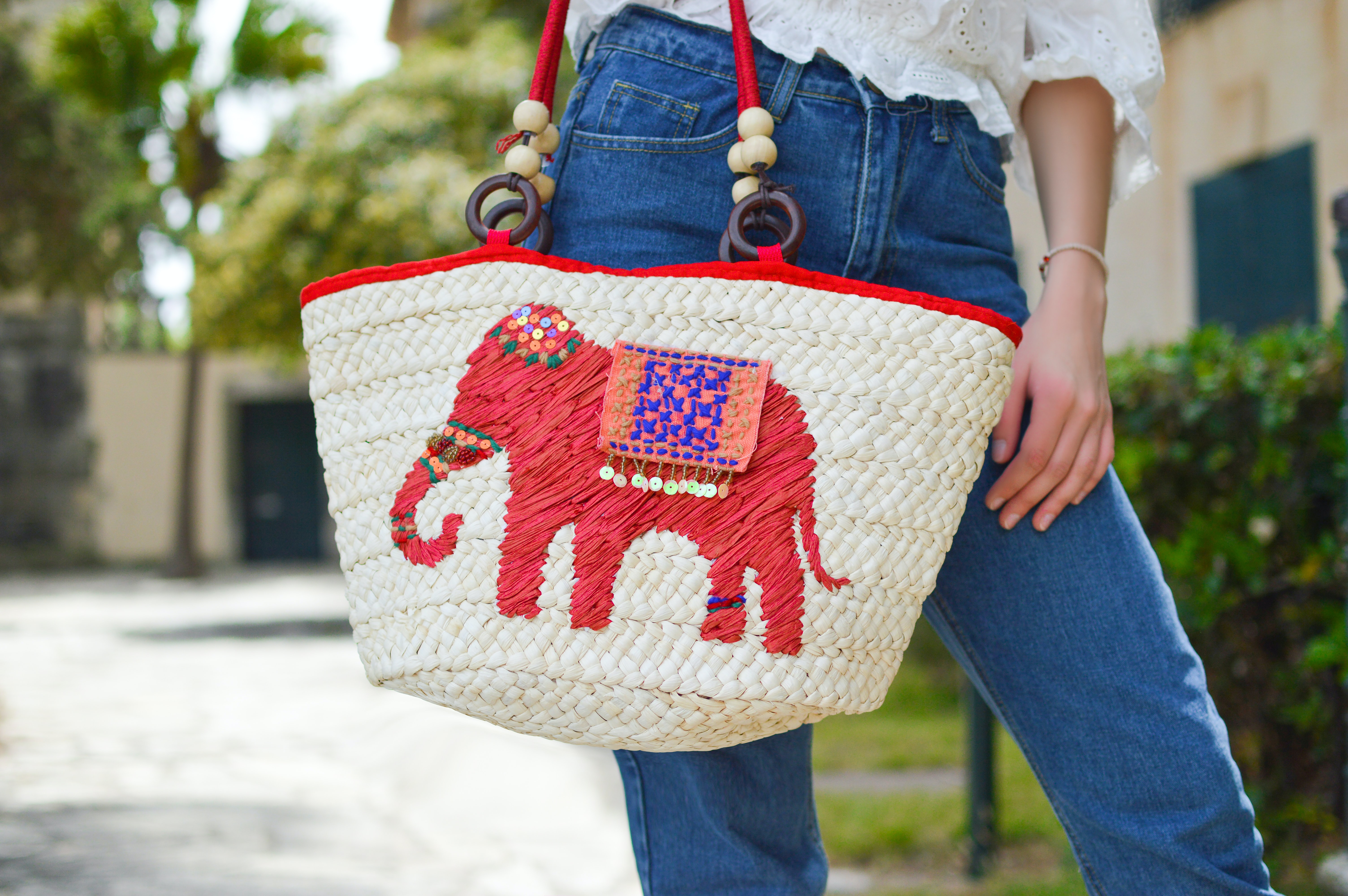 A person holds a colorful woven bag with a red embroidered elephant outdoors in Corfu