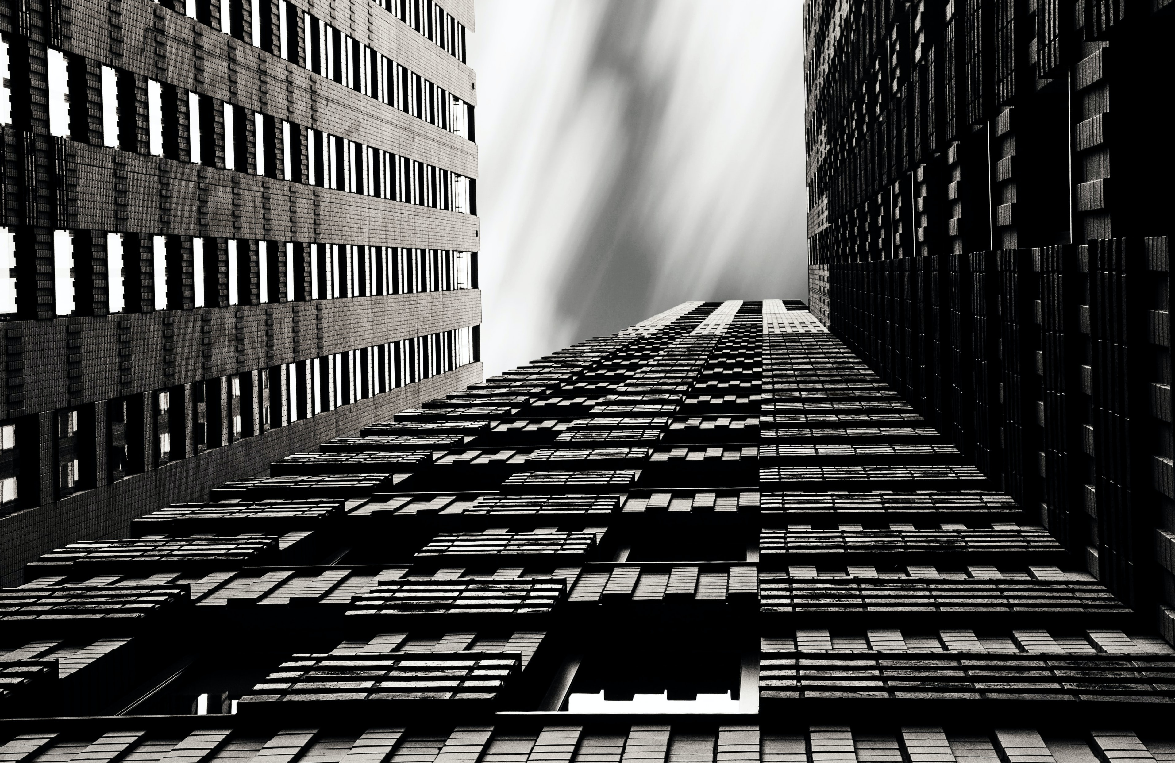 A black-and-white shot of skyscrapers with geometric patterns facade.