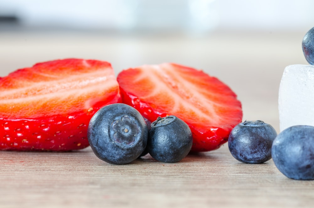selective focus photography of strawberry and blueberries