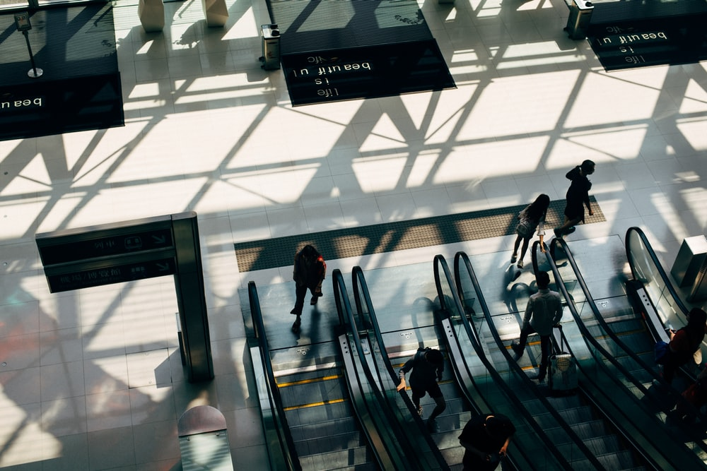 people riding on escalator
