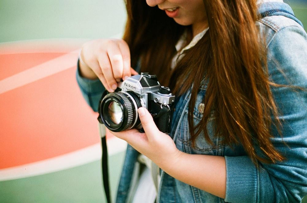 woman holding black bridge camera during daytime