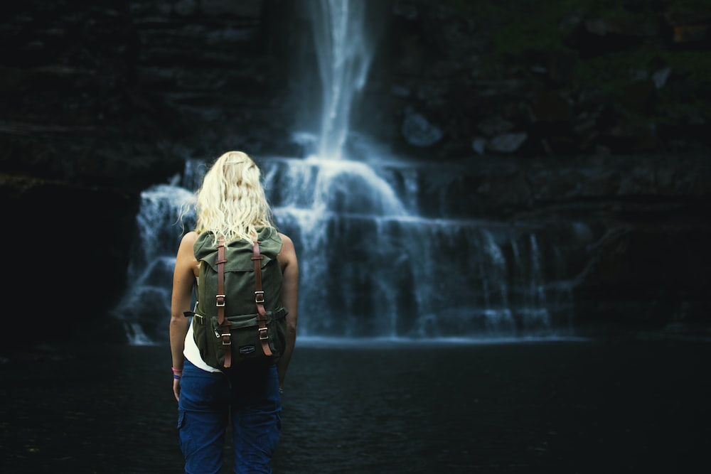 shallow focus photography of woman with backpack in front of water falls