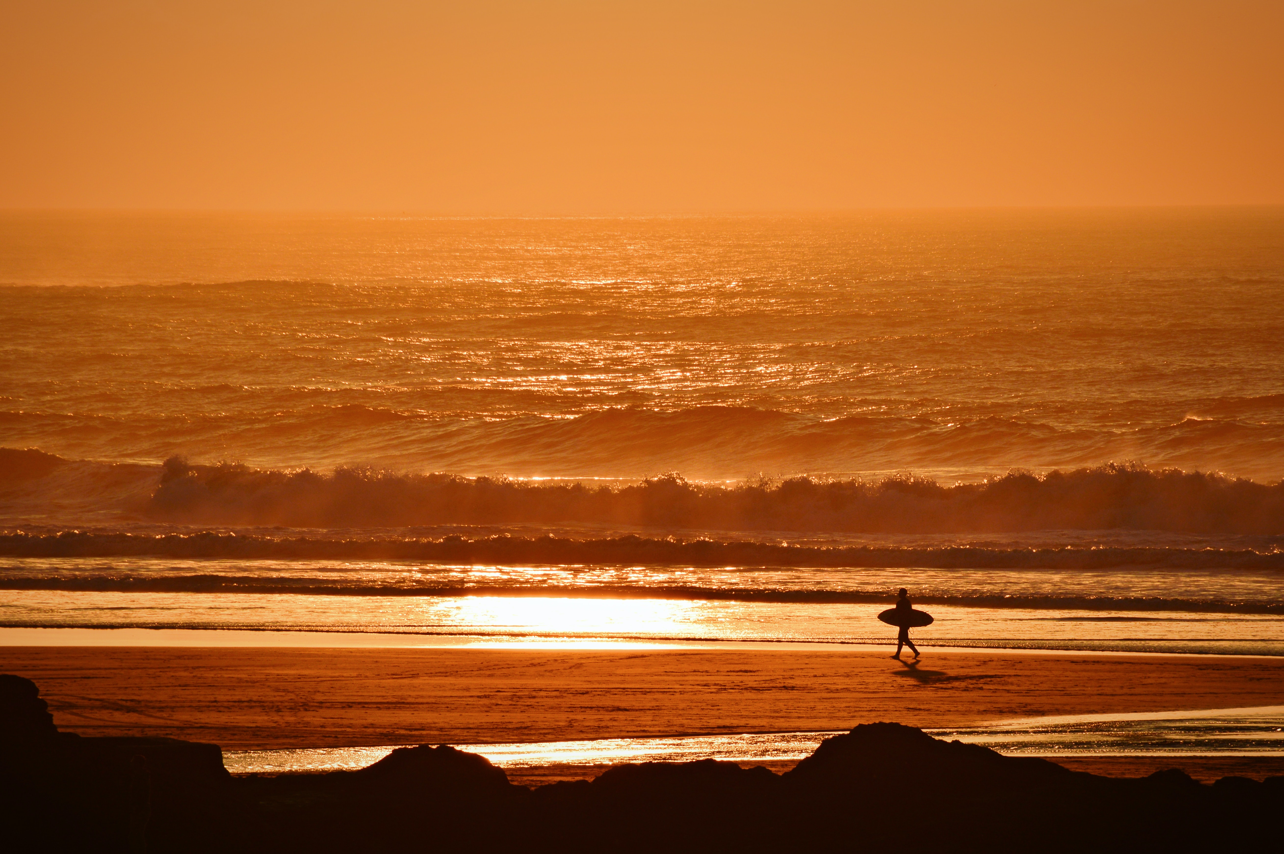Surfer walking down the Perranporth sand Beach at sunset