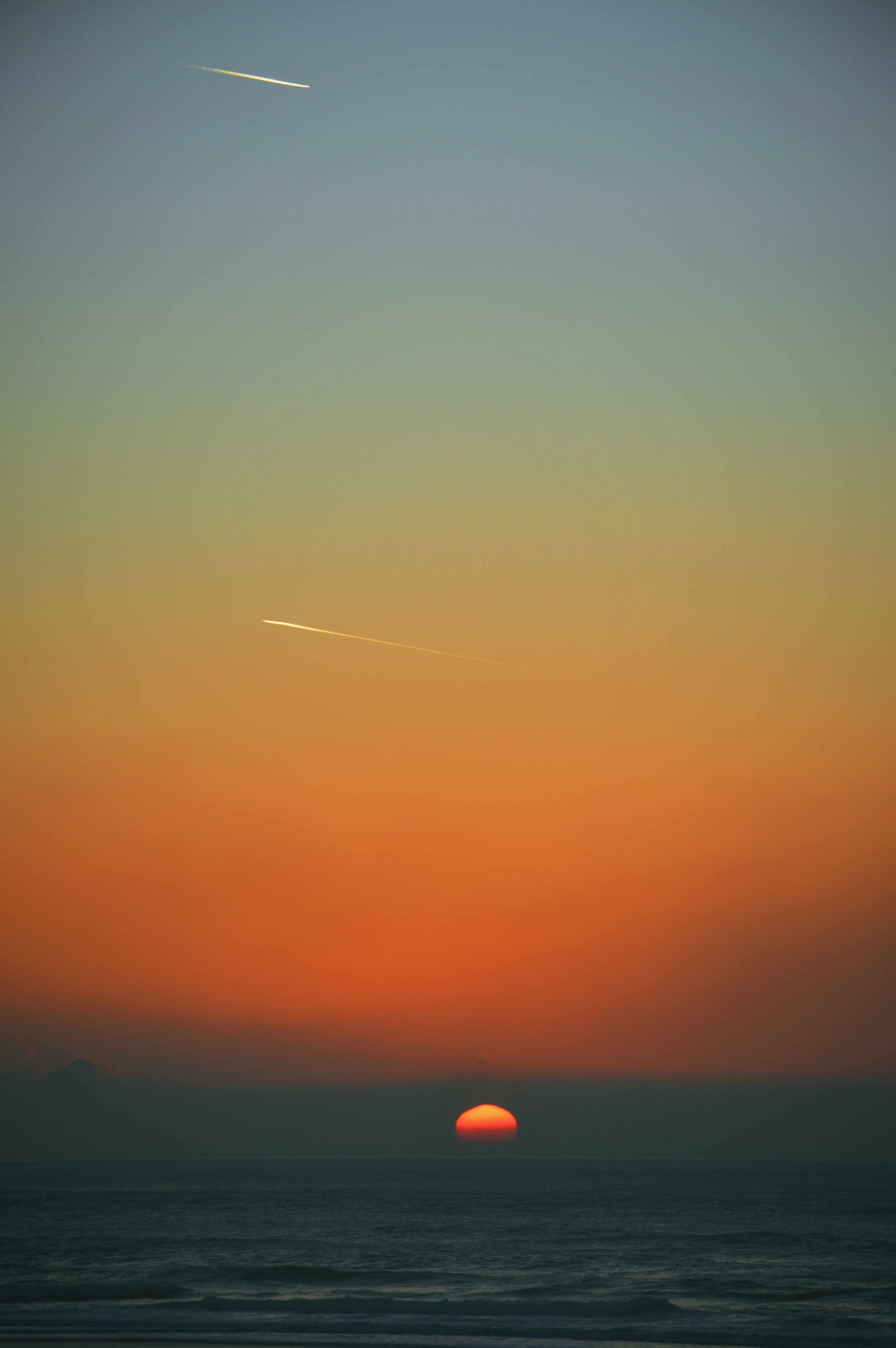 Shooting stars and the setting sun over the sea at Perranporth Beach