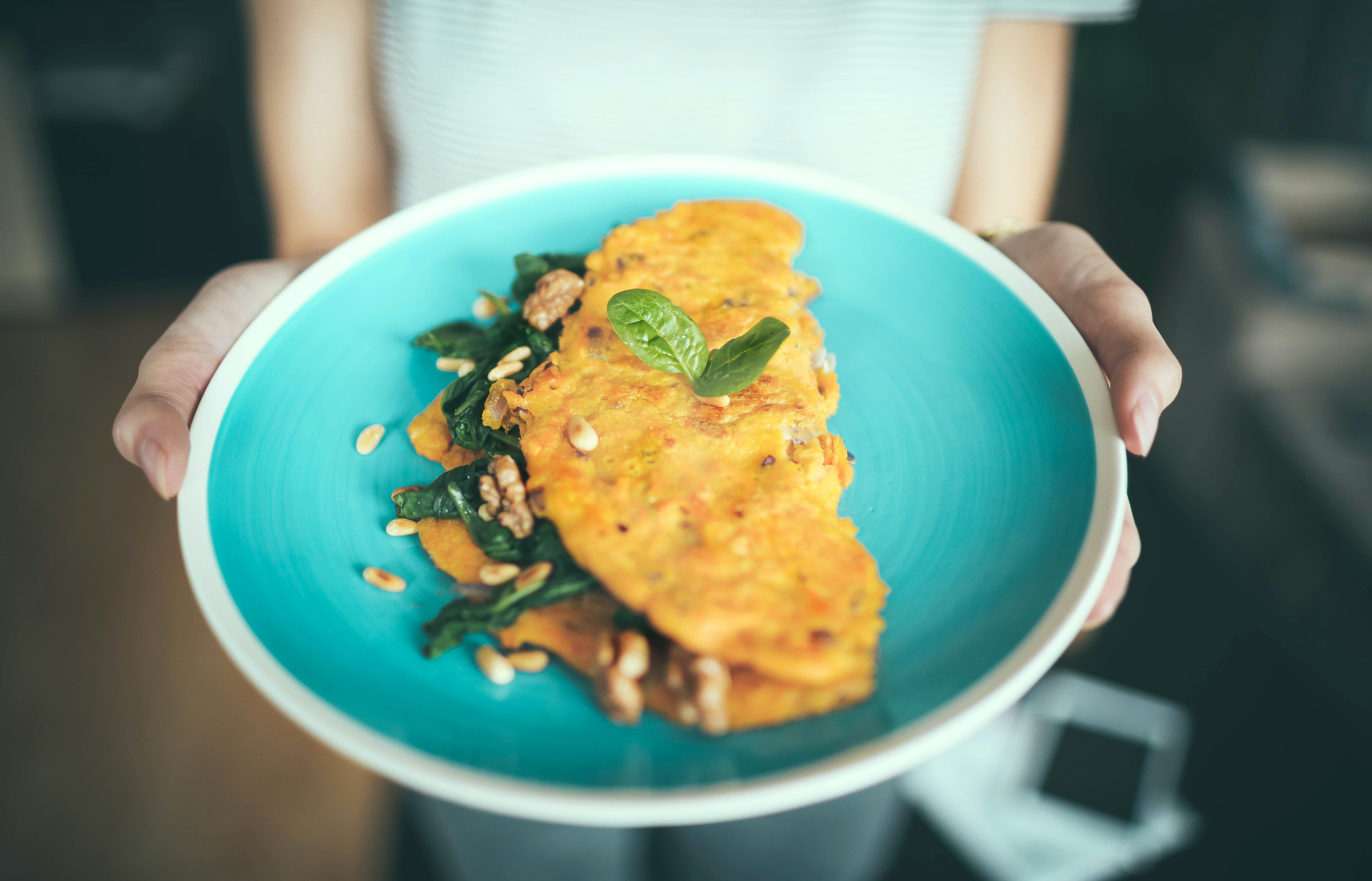 Woman holding an aquamarine plate with an omelette on it garnished with herbs