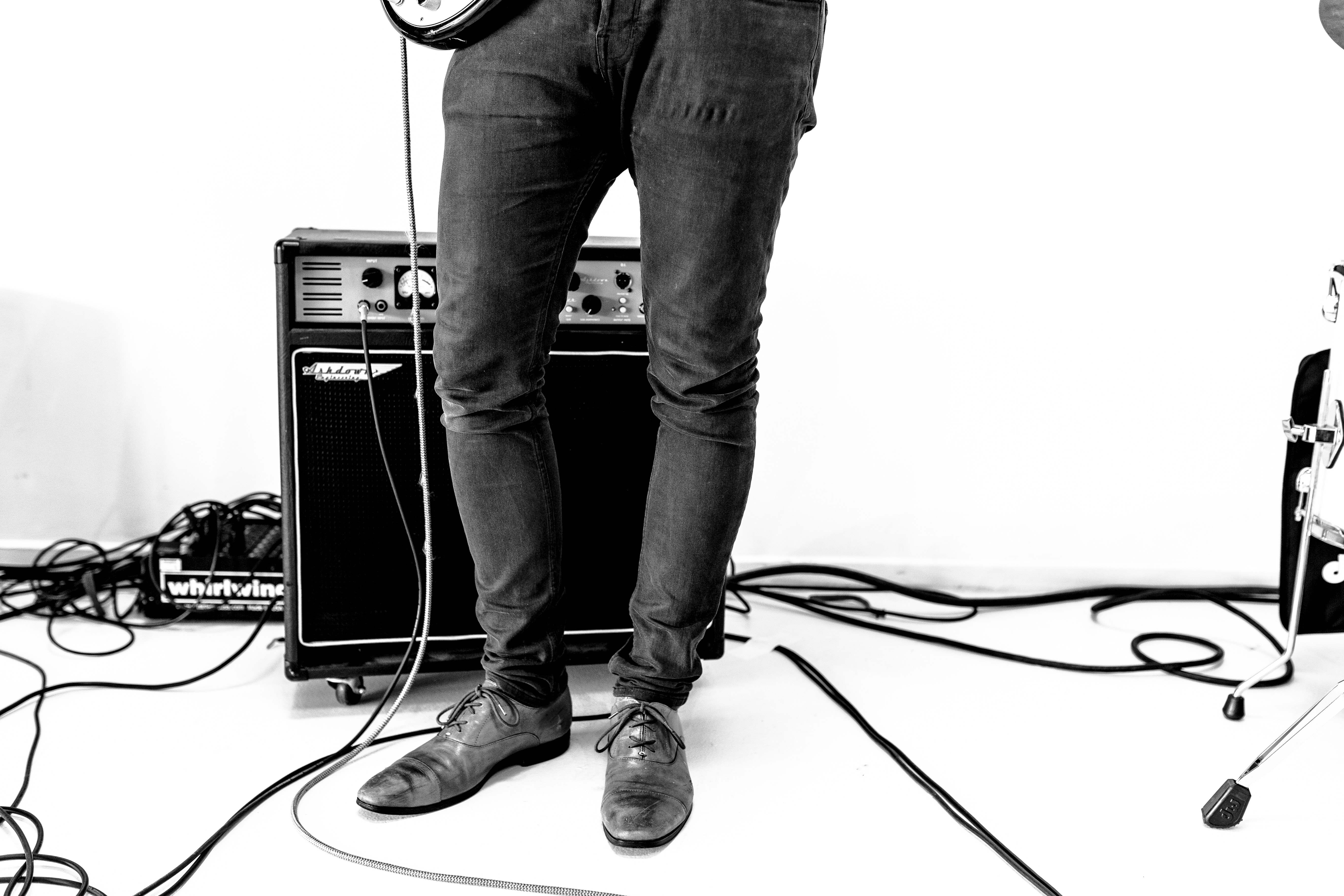 A black-and-white shot of a person in jeans playing the guitar next to an amplifier