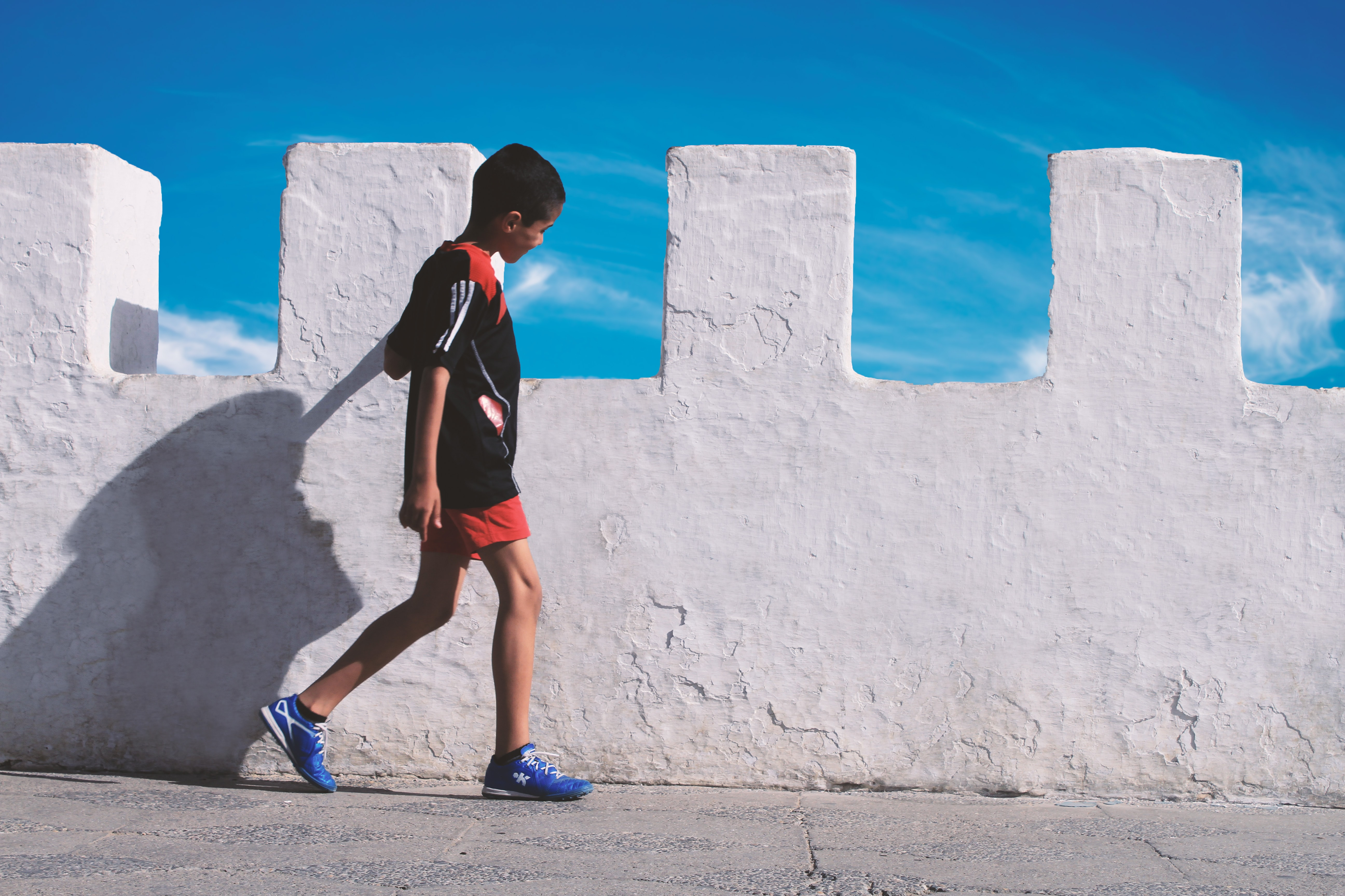 boy walking beside white concrete wall