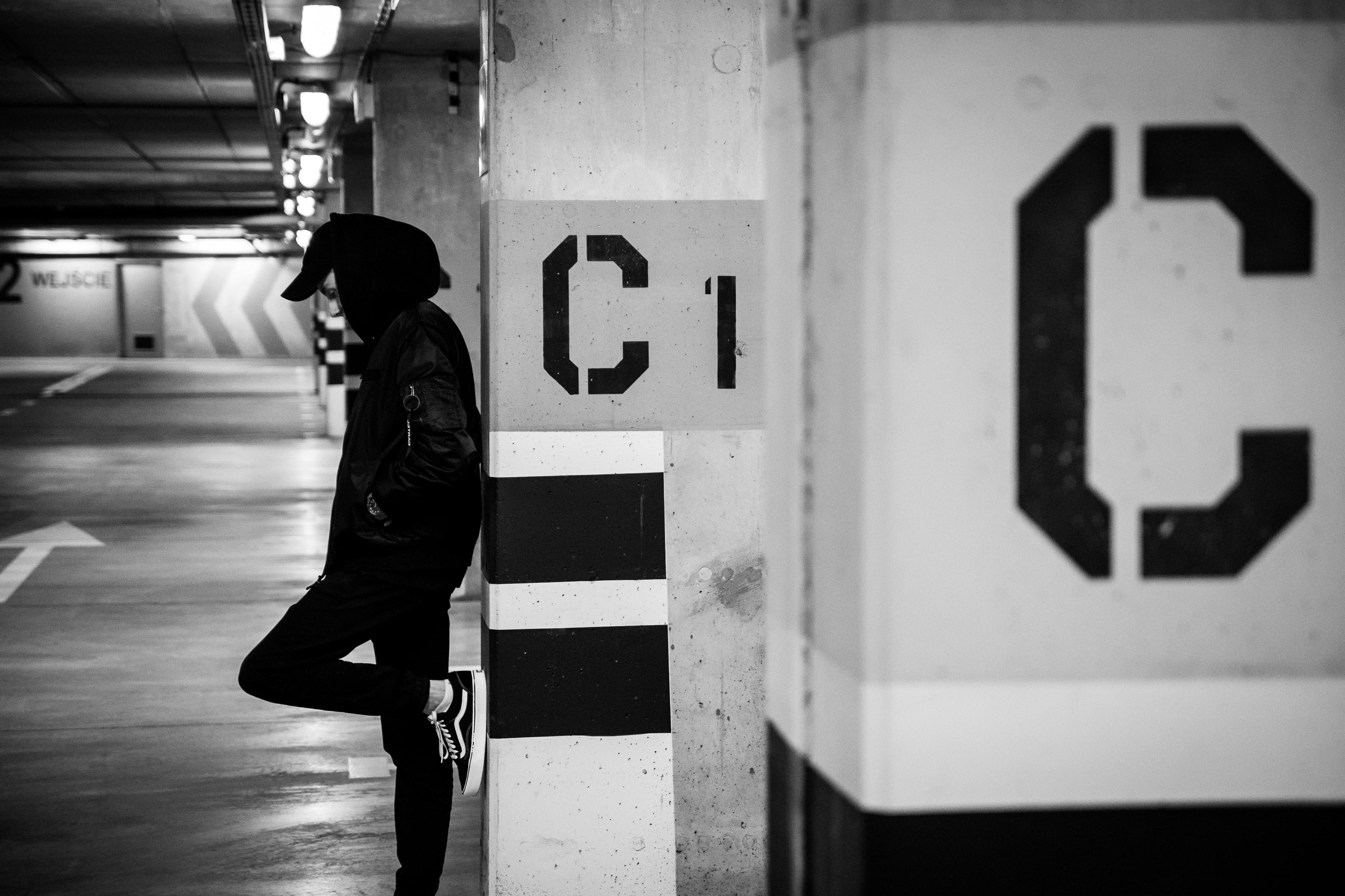 Black and white shot standing and leaning against underground car park pillar with C sign