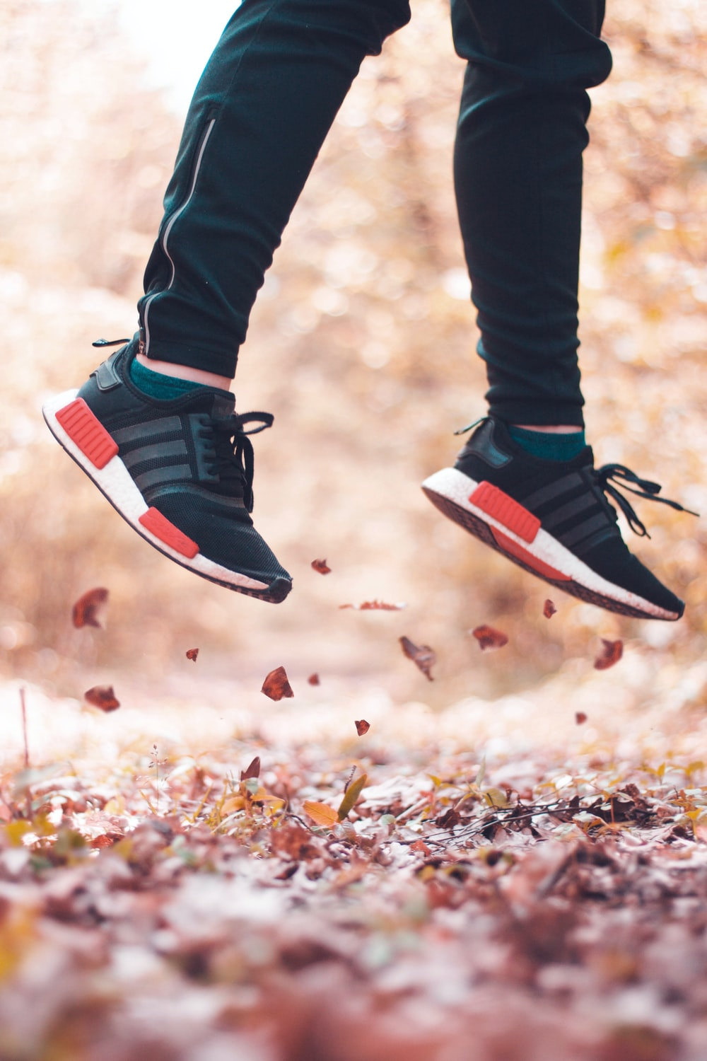 person jumping from leaves