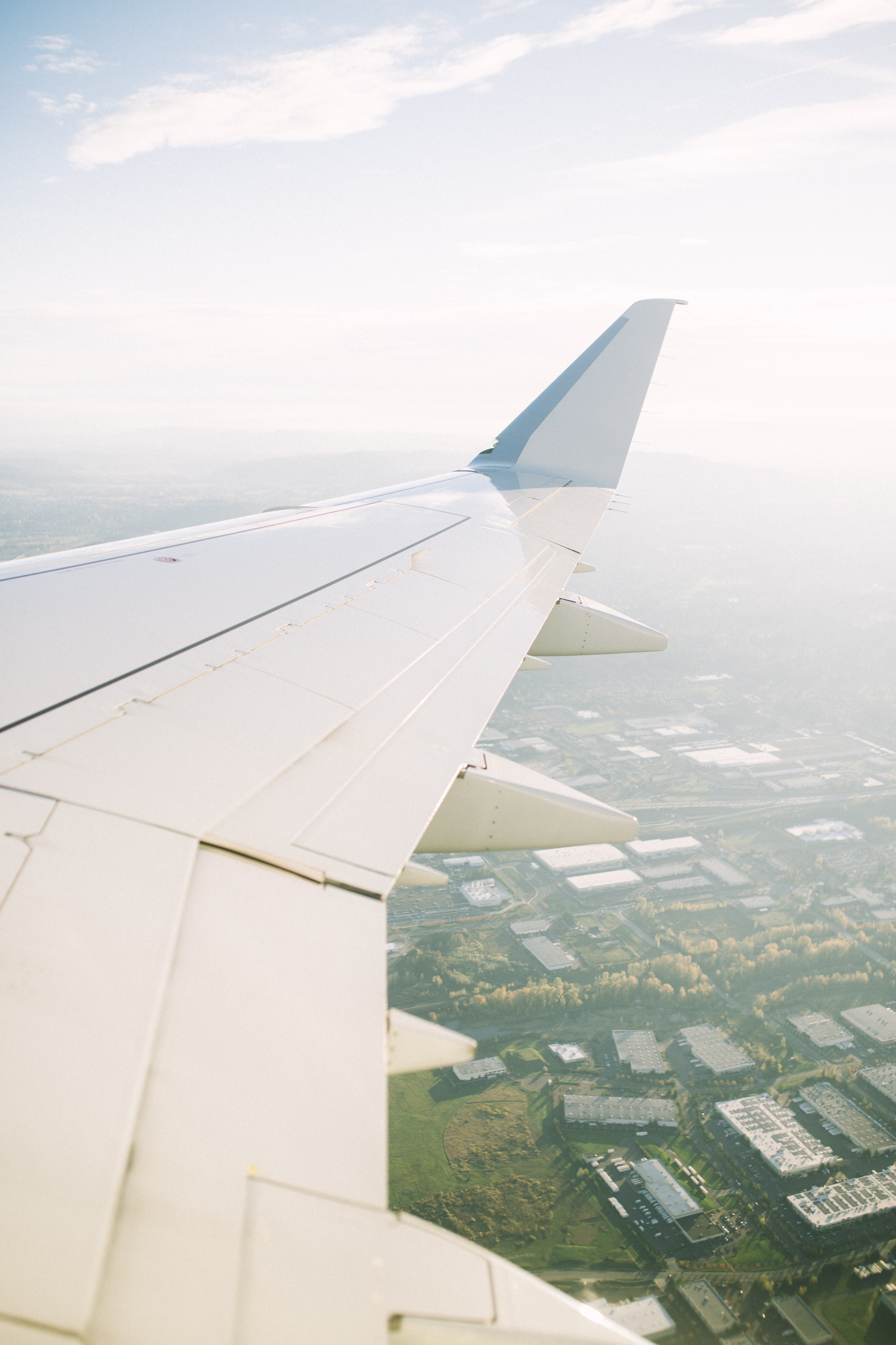A view from an airplane window on its wing and a town underneath