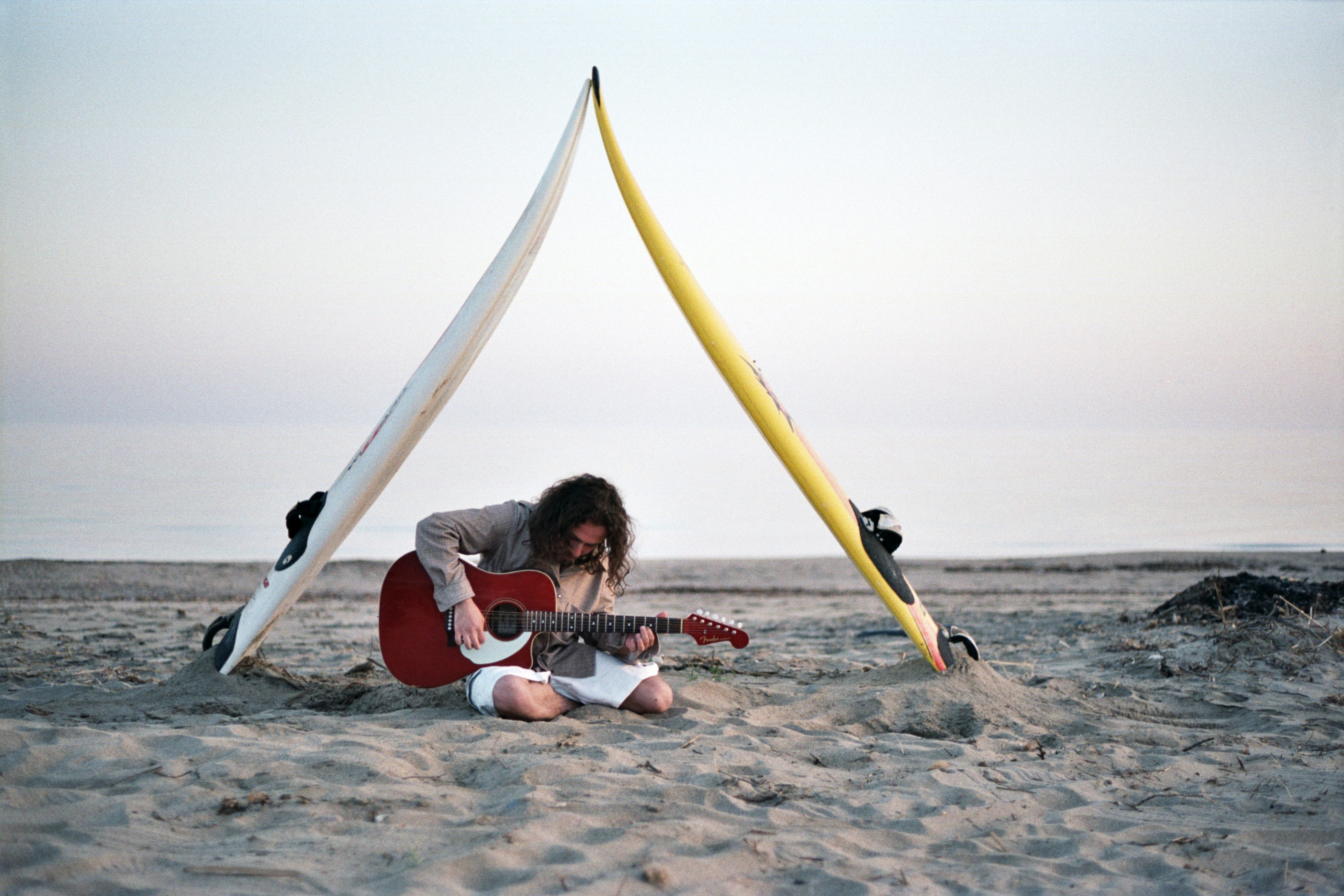 Man sitting on the beach, playing guitar under two surfboards at Imbros