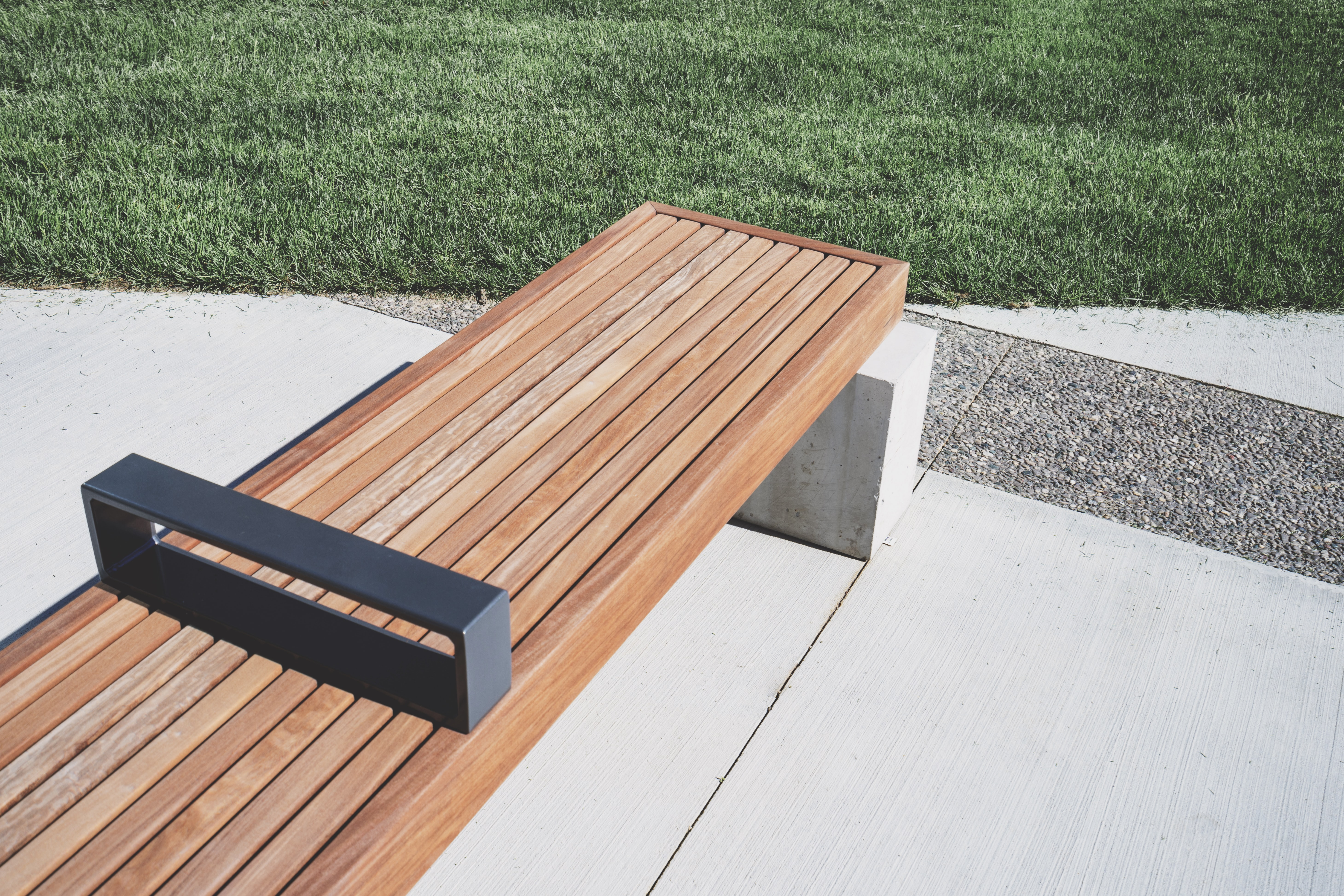 A flat wooden bench on concrete near a green lawn