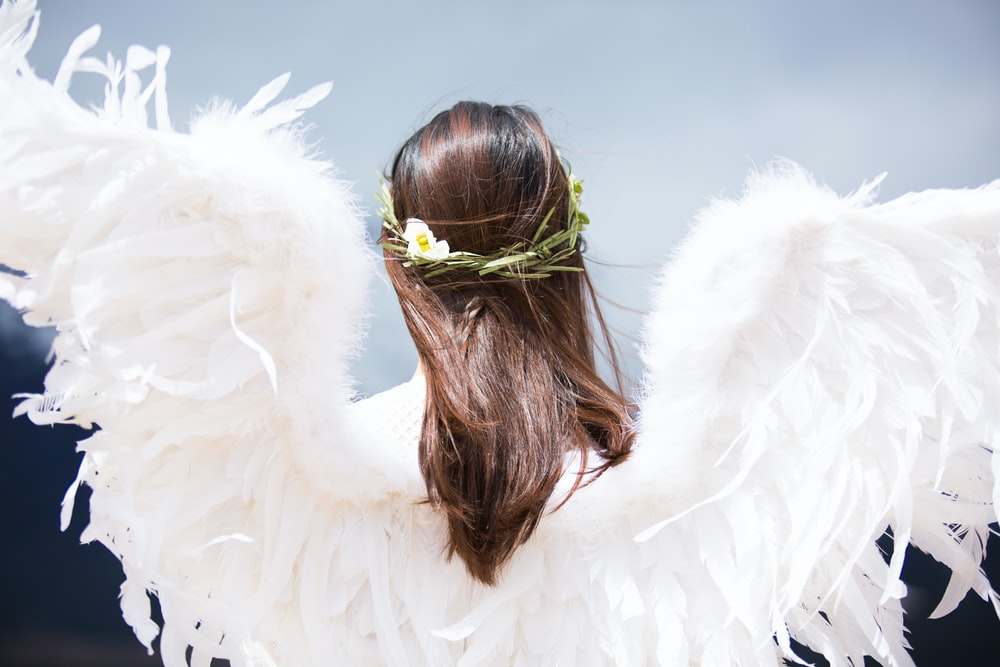 Woman dressed as an angel with feather wings and a flower crown