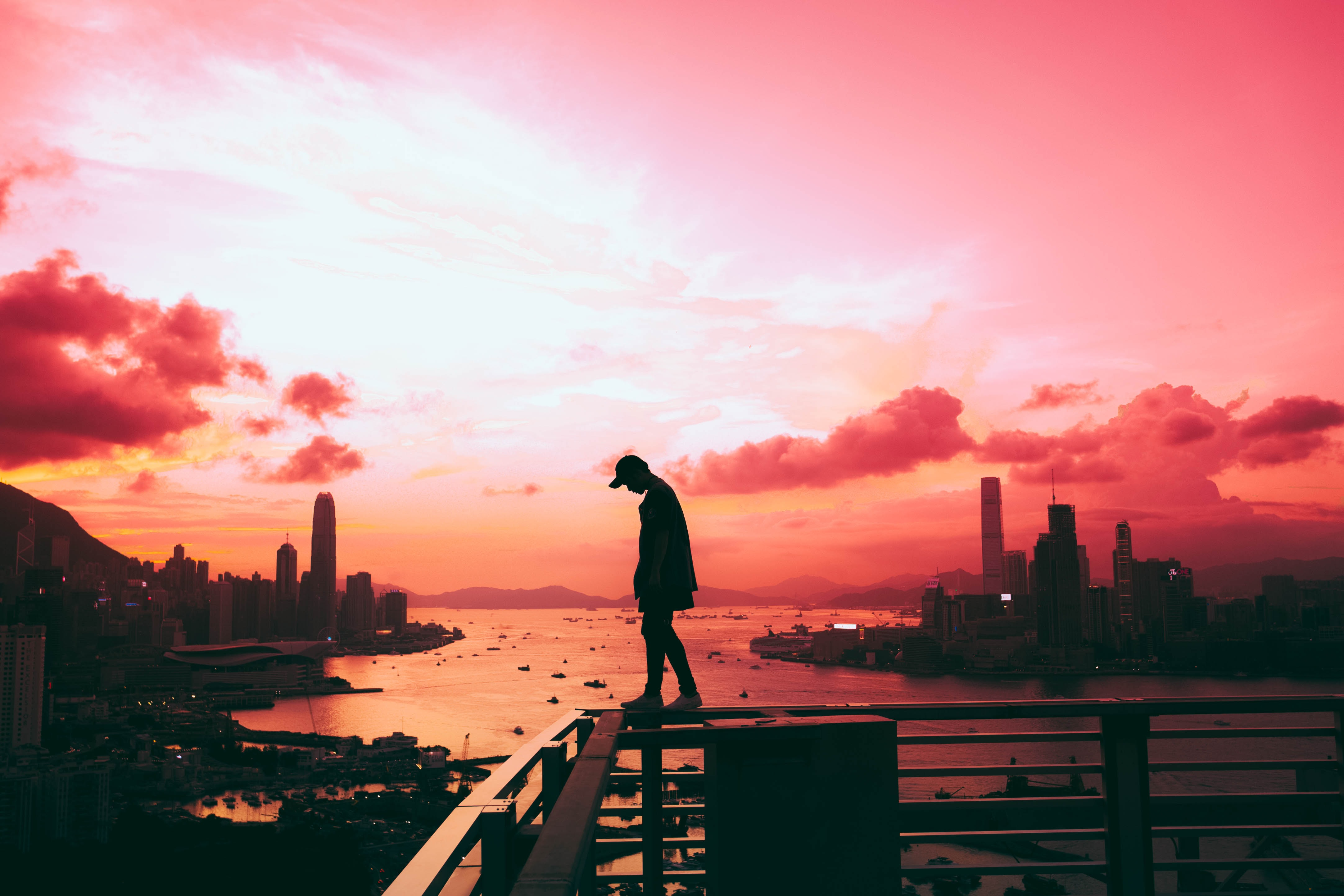 silhouette of person standing on railing