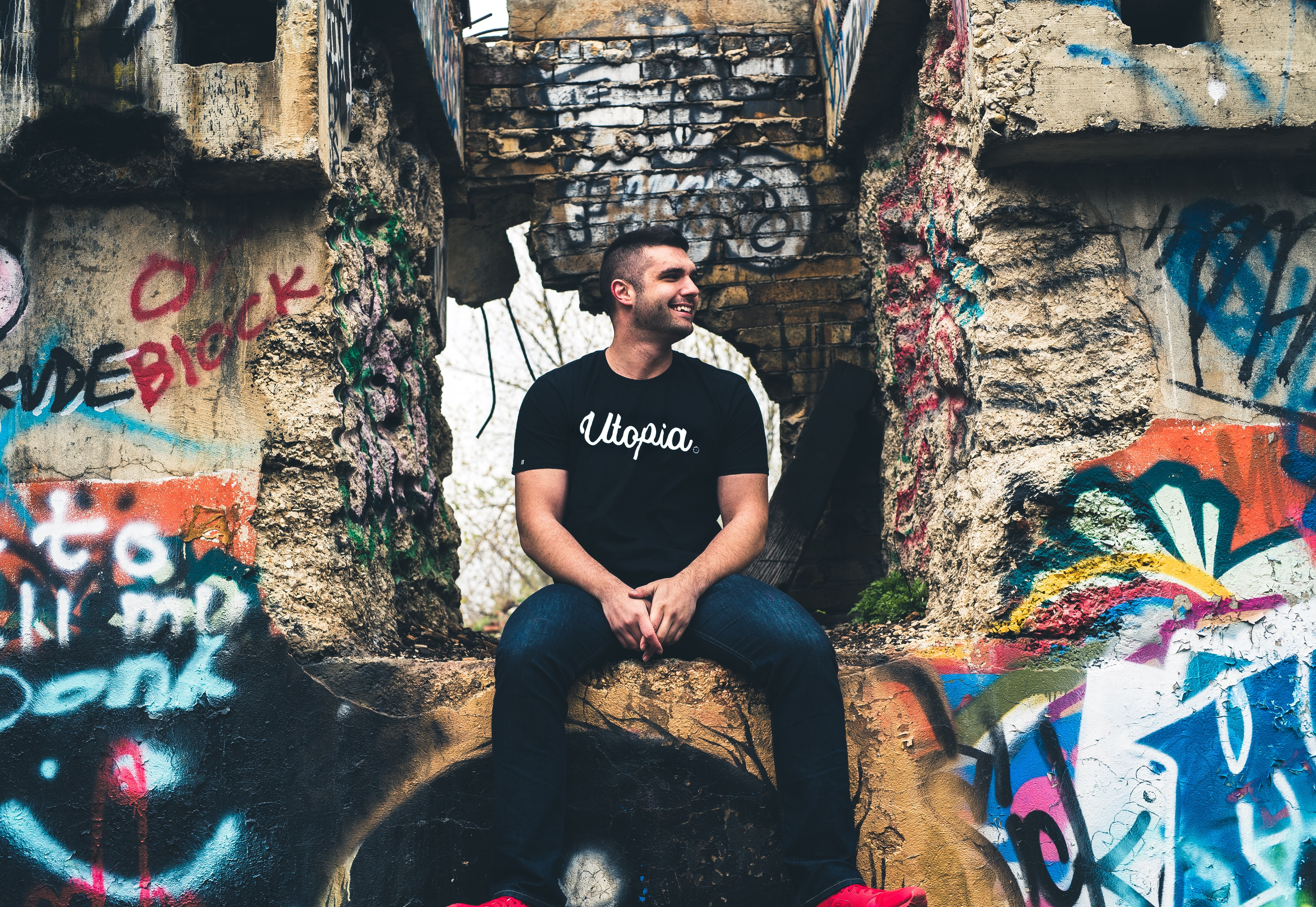 "Man in a t-shirt reading ""Utopia"" smiles to the side while sitting among concrete graffitied walls"