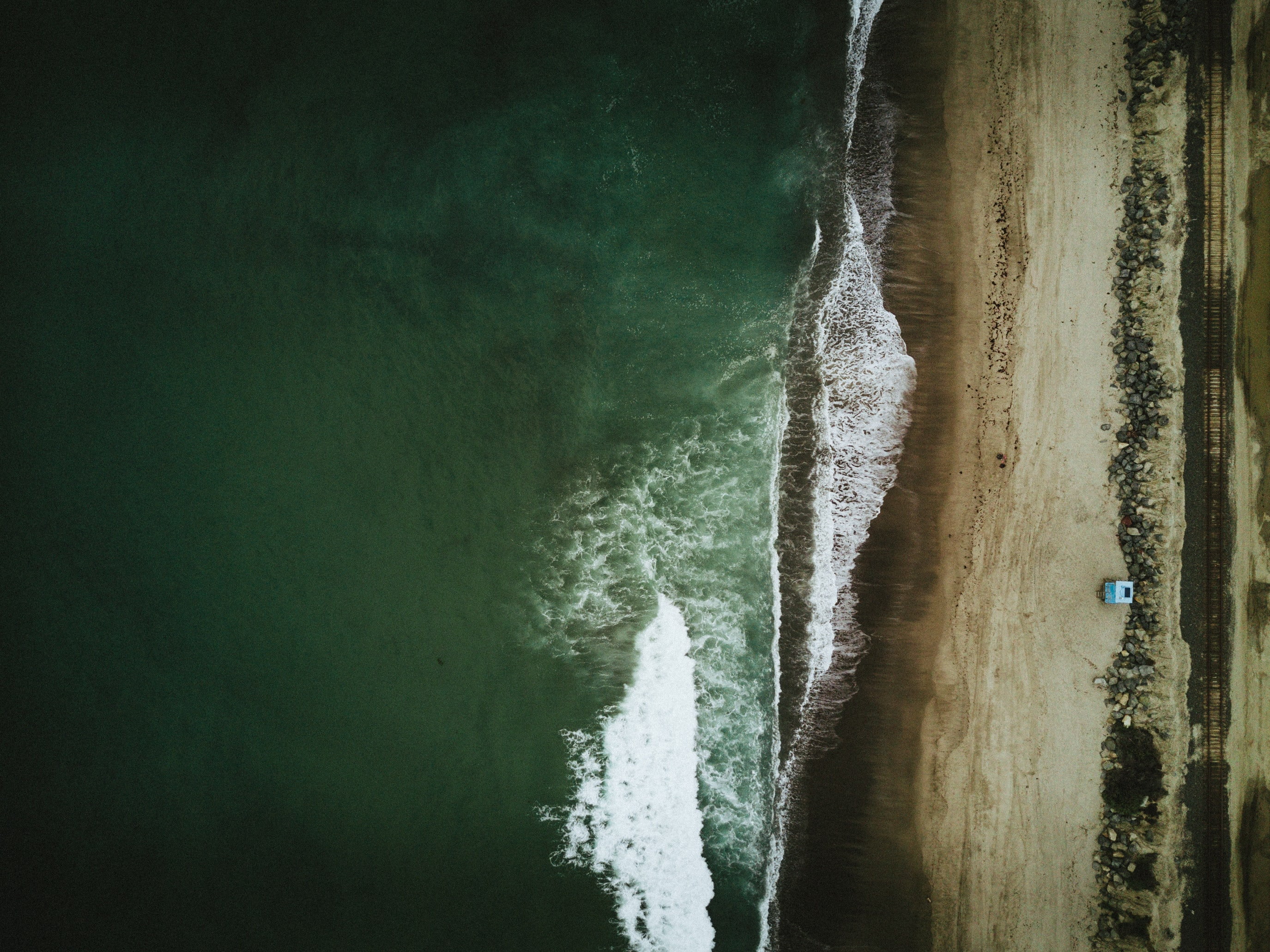 Drone aerial view of the ocean washing on a sand beach at San Clemente