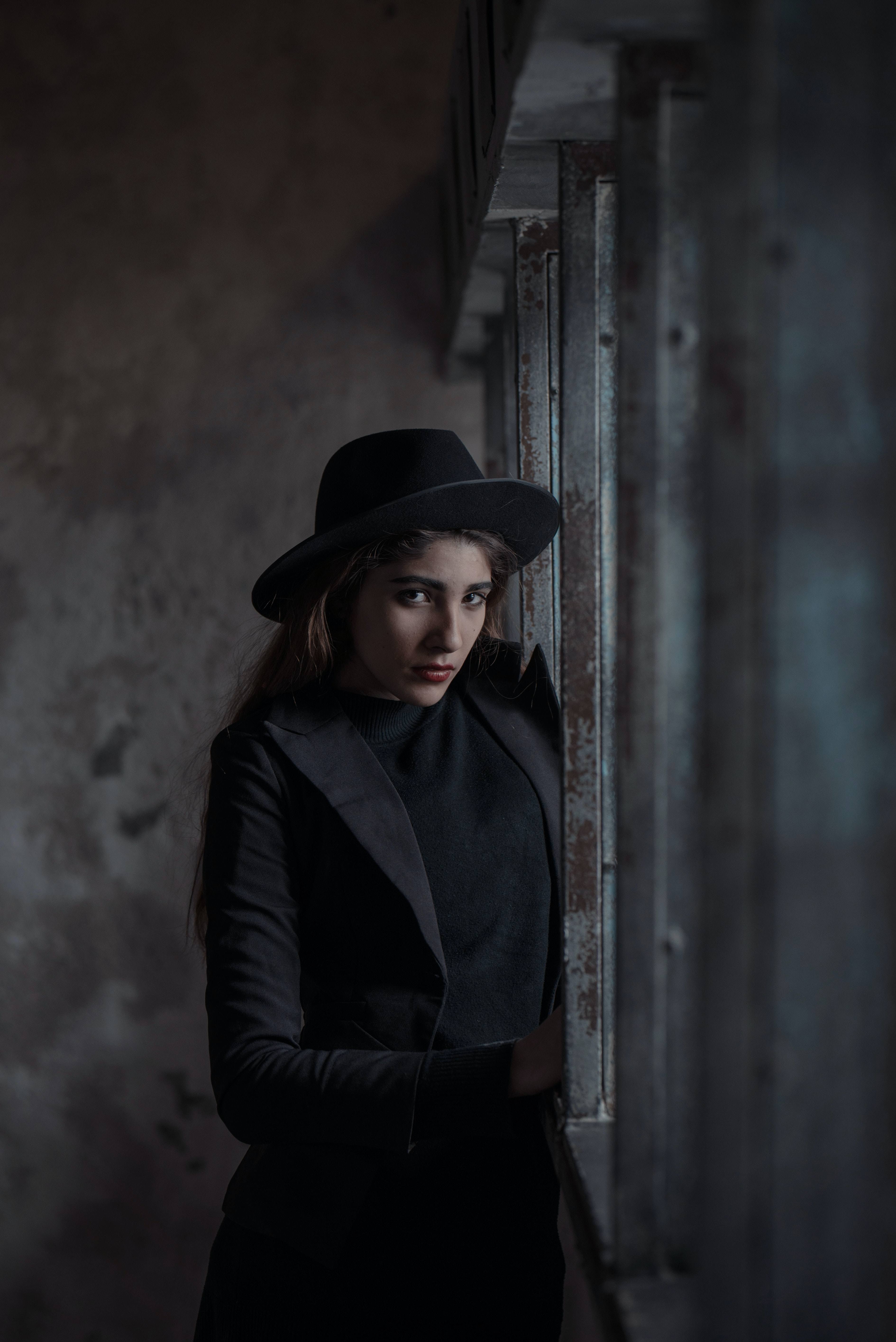 Woman in a black outfit looks up skeptically in an abandoned building