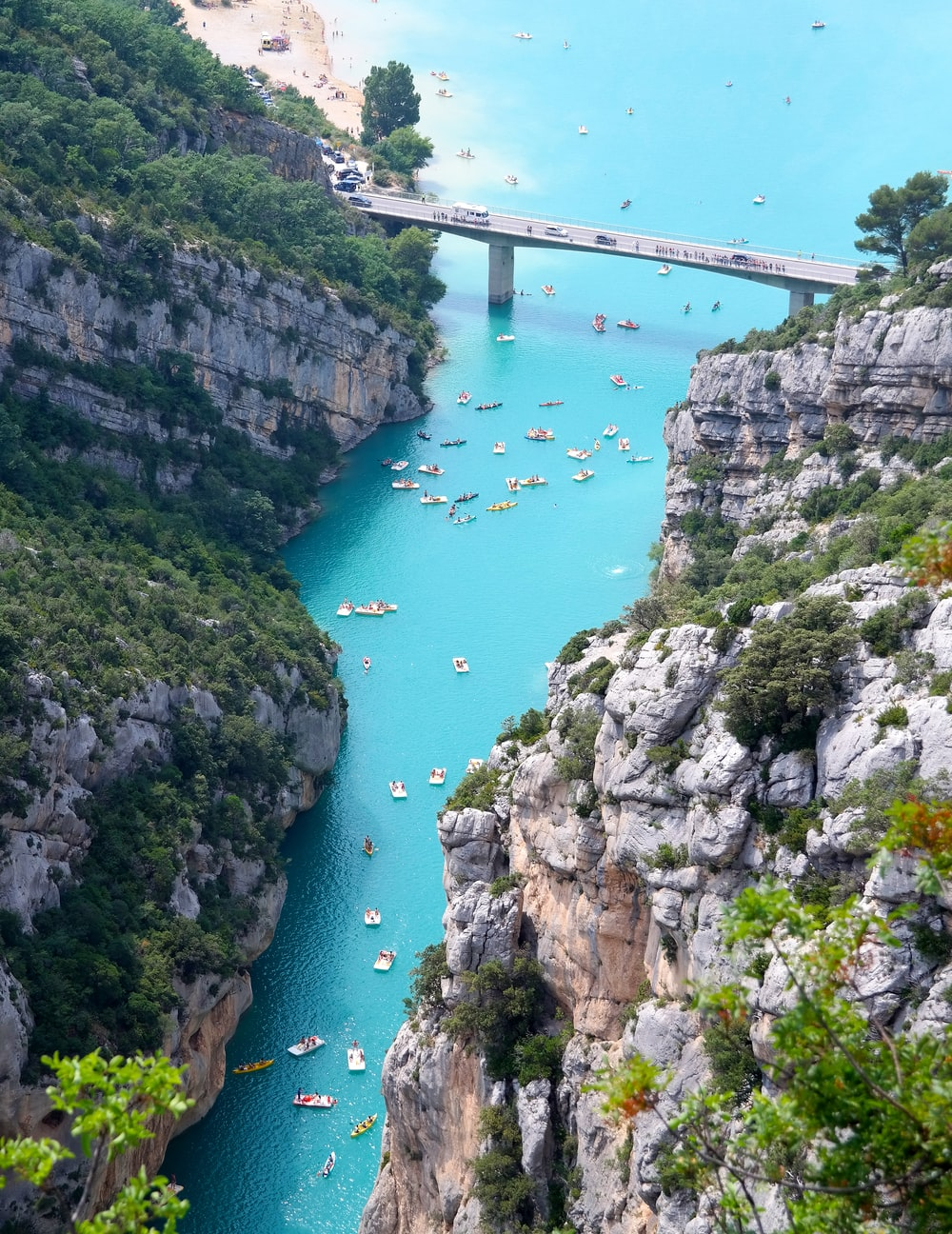 aerial view of boats on body of water beside mountain