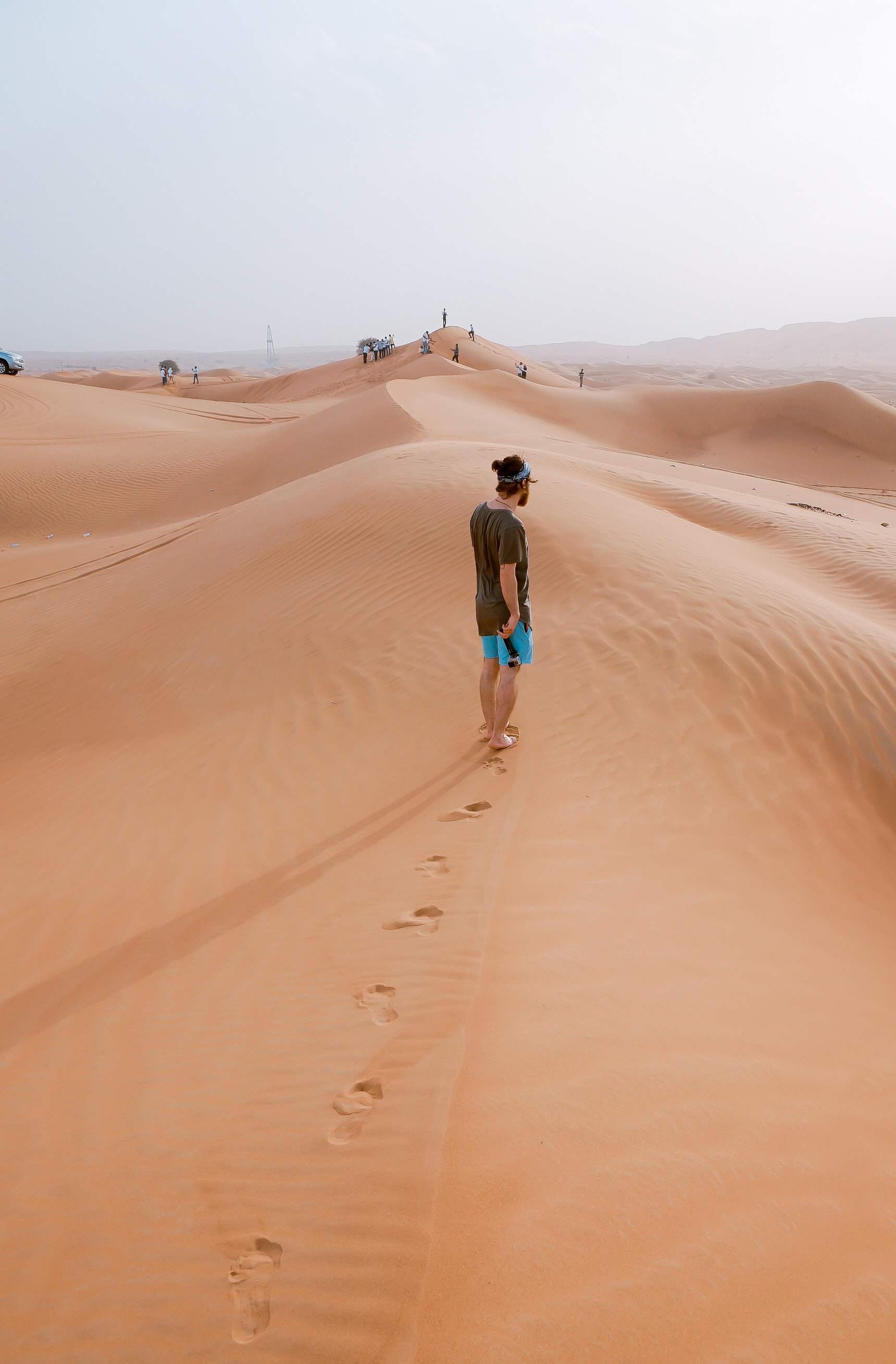 Hiker walks alone in the sands of Desert Retreat Camp