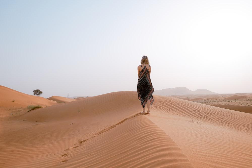 woman walking on desert during daytime