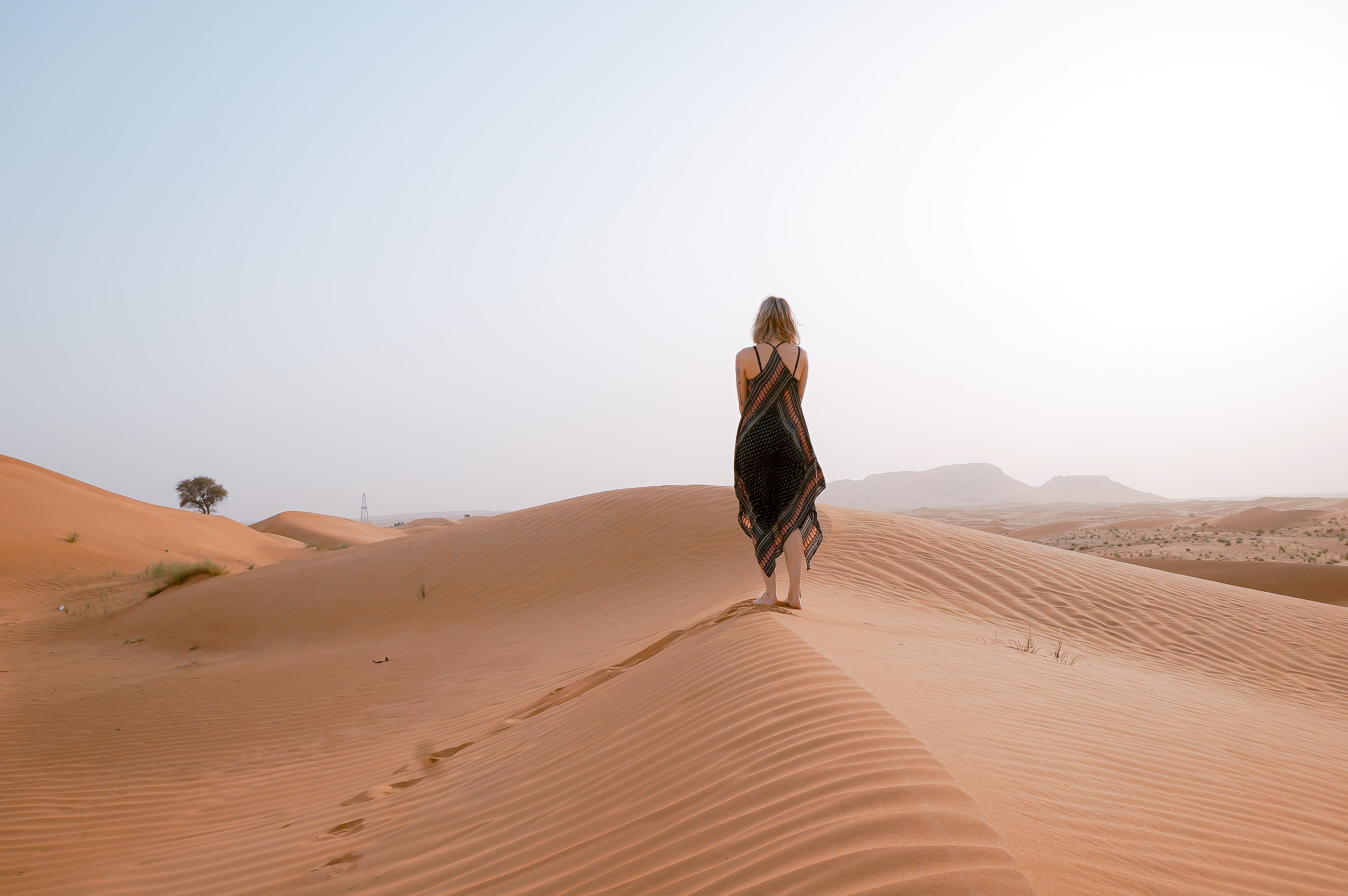 Fashionable woman walks through the dry sandy deserts of Safari Dubai
