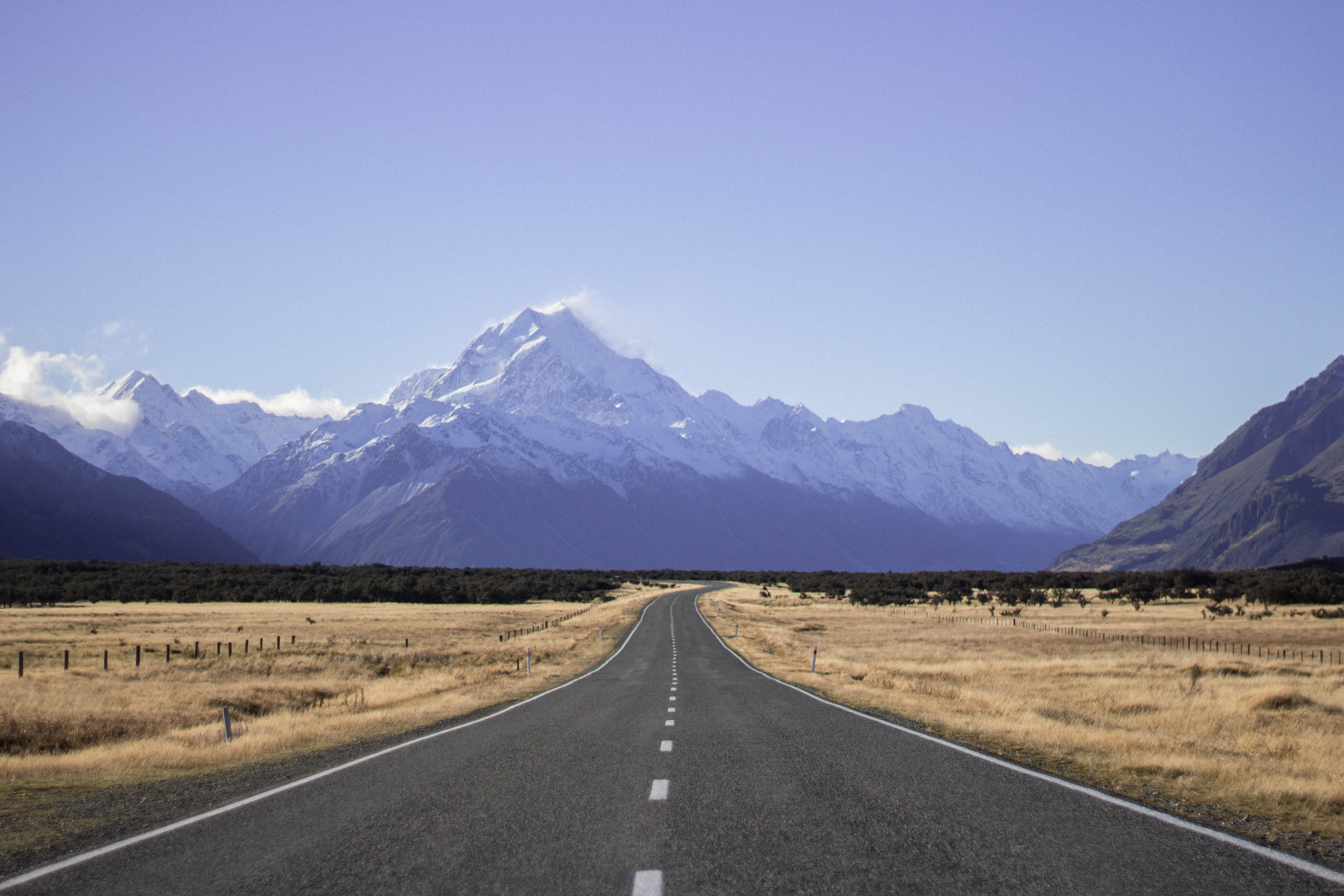landscape photography of empty dessert road under blue calm sky with mountain view