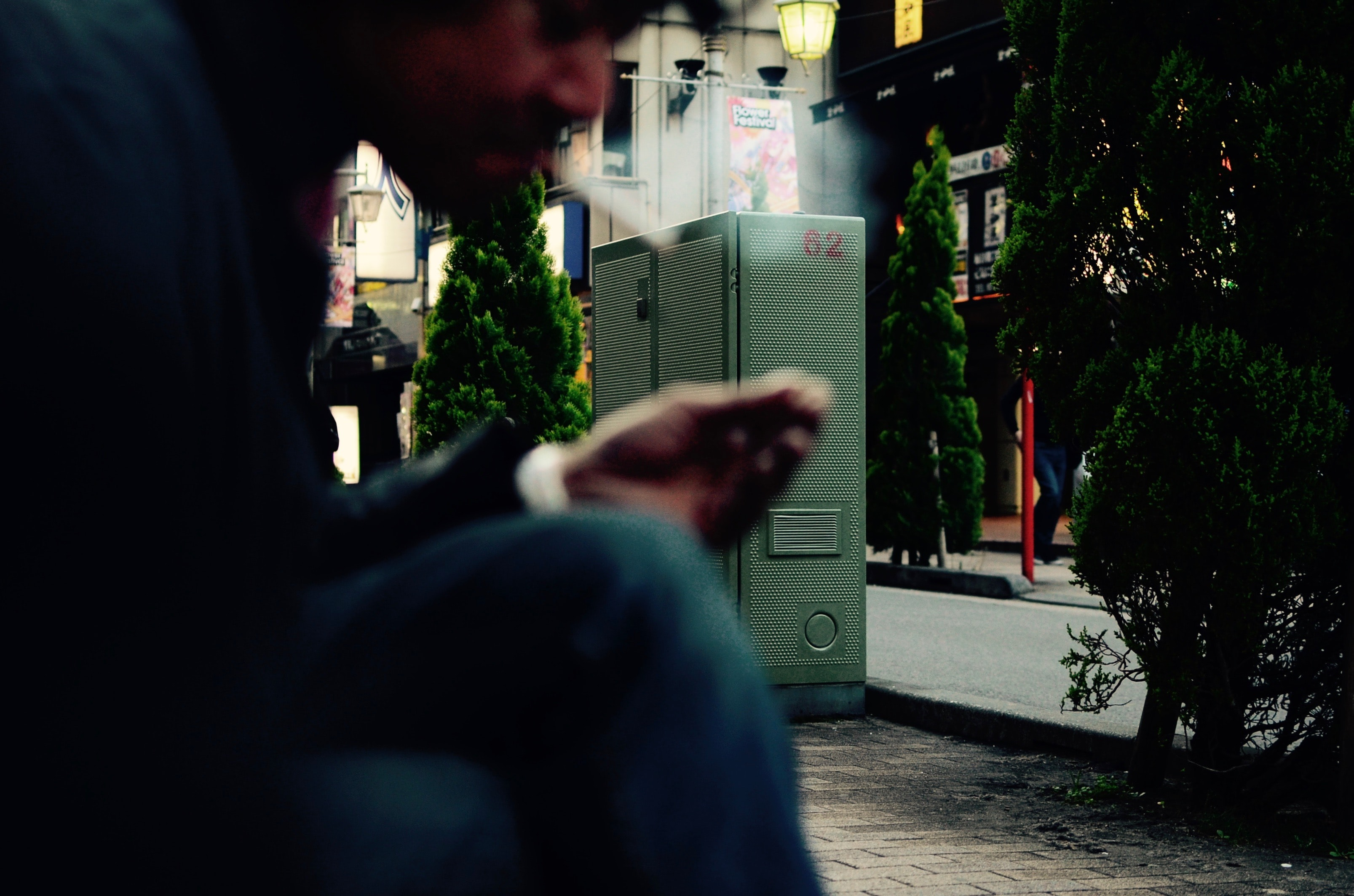 A bearded man puffing a cigarette in the foreground with a numbered generator in the background on a street flanked by stores and trees