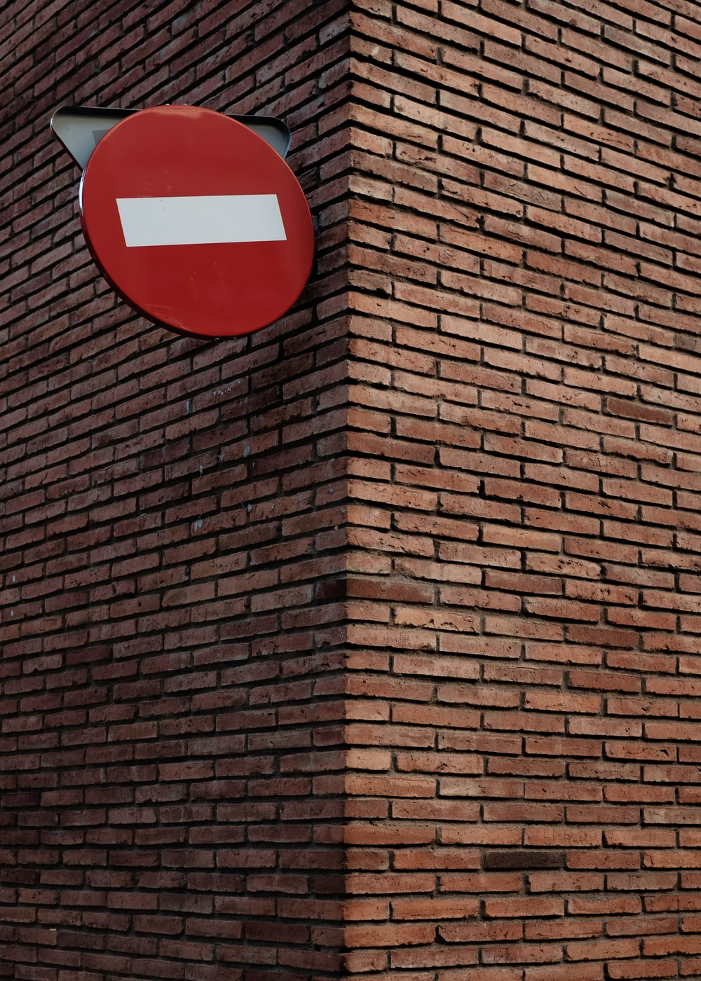 red and white signage on red brick wall at daytime