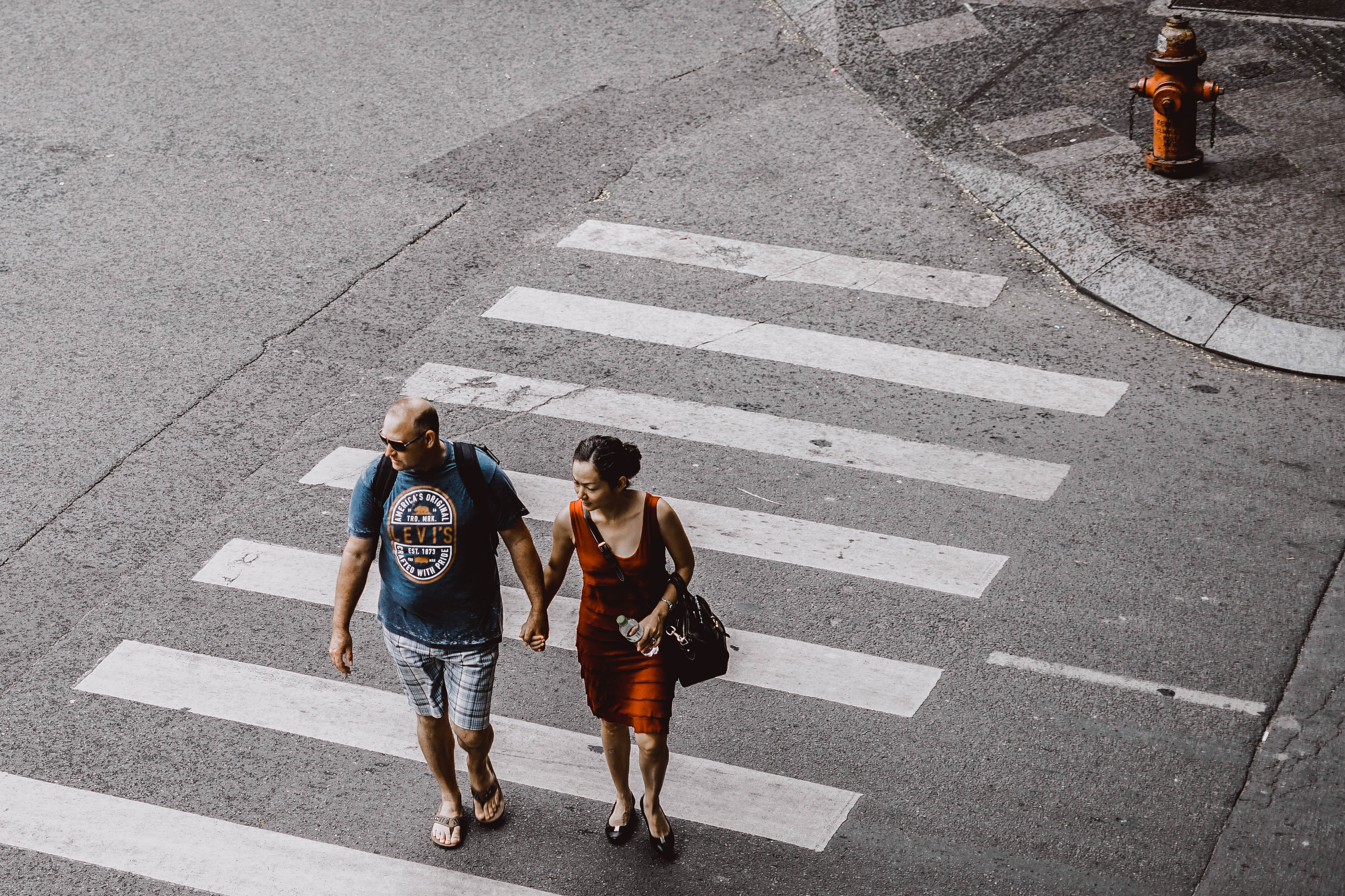 man and woman walking on pedestrian lane during daytime