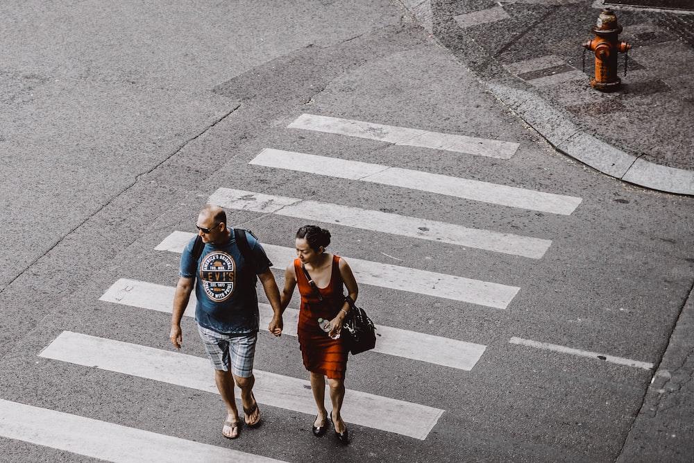 man and woman walking on pedestrian lane during daytime