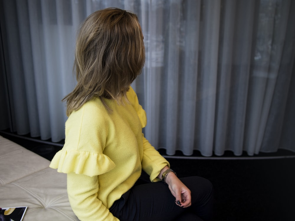 woman sitting on leather cushion beside glass window