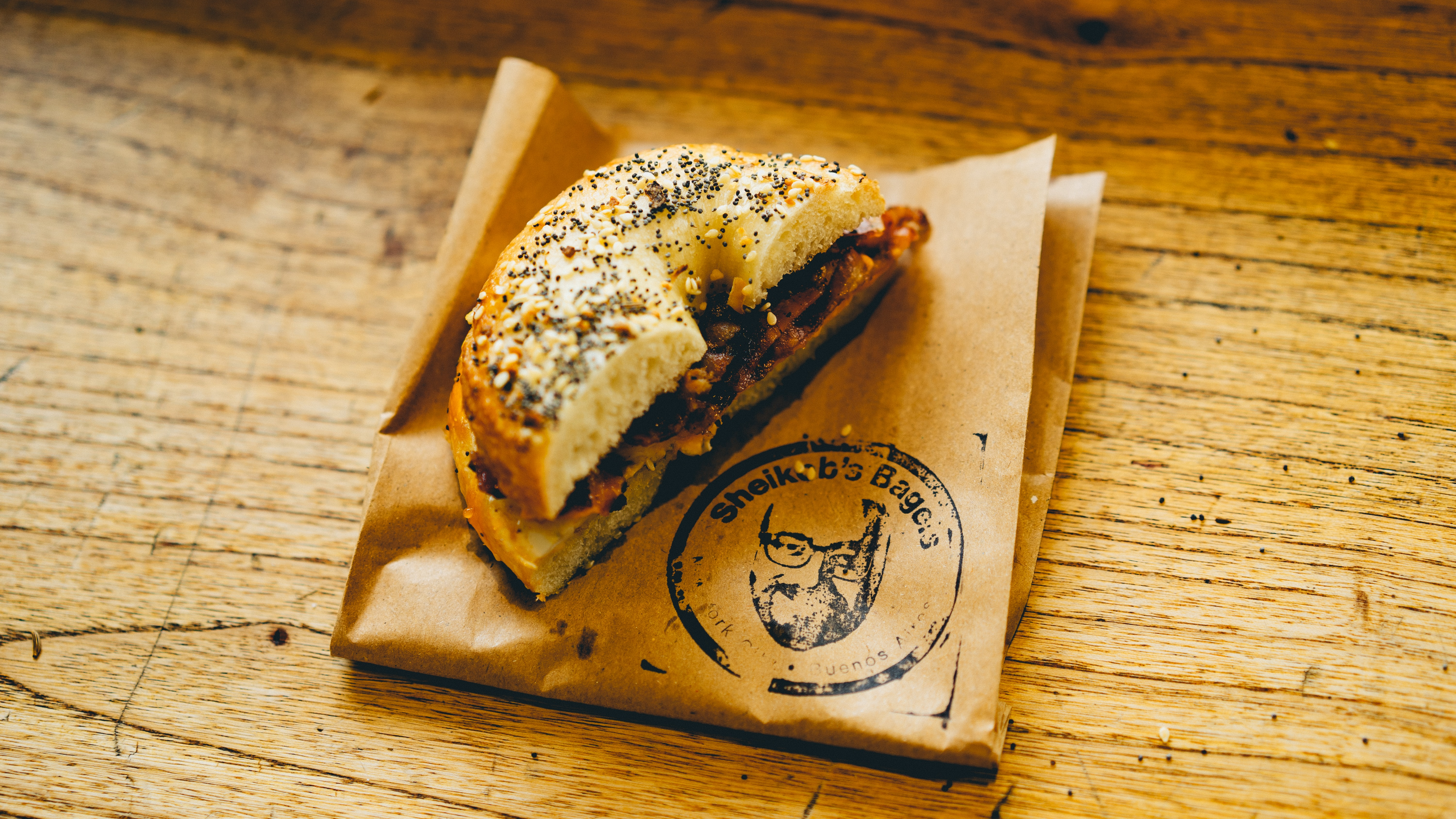 A bacon egg bagel covered in poppy and sesame seeds on top of a brown paper bag labeled Shekob's Bagels