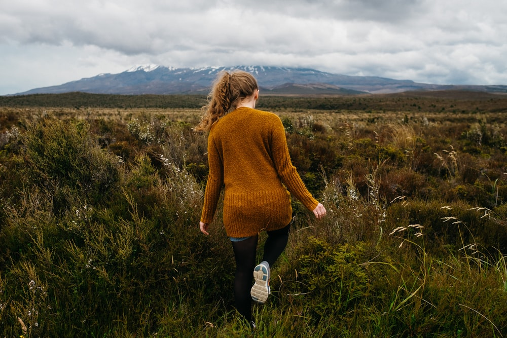 woman walking in grass field under stratocomulus clouds