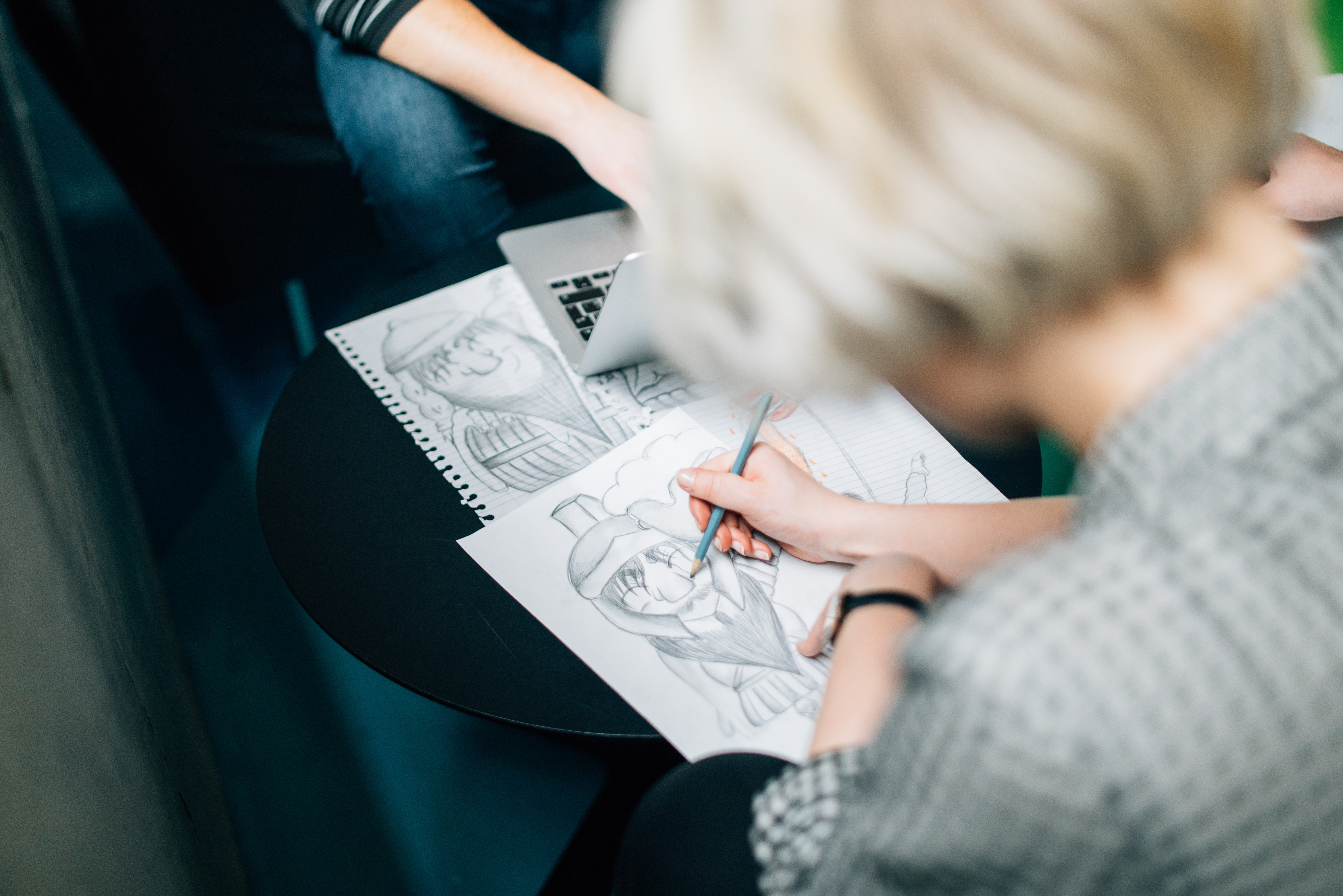 A caucasian female drawing and sketching a character with her pencil