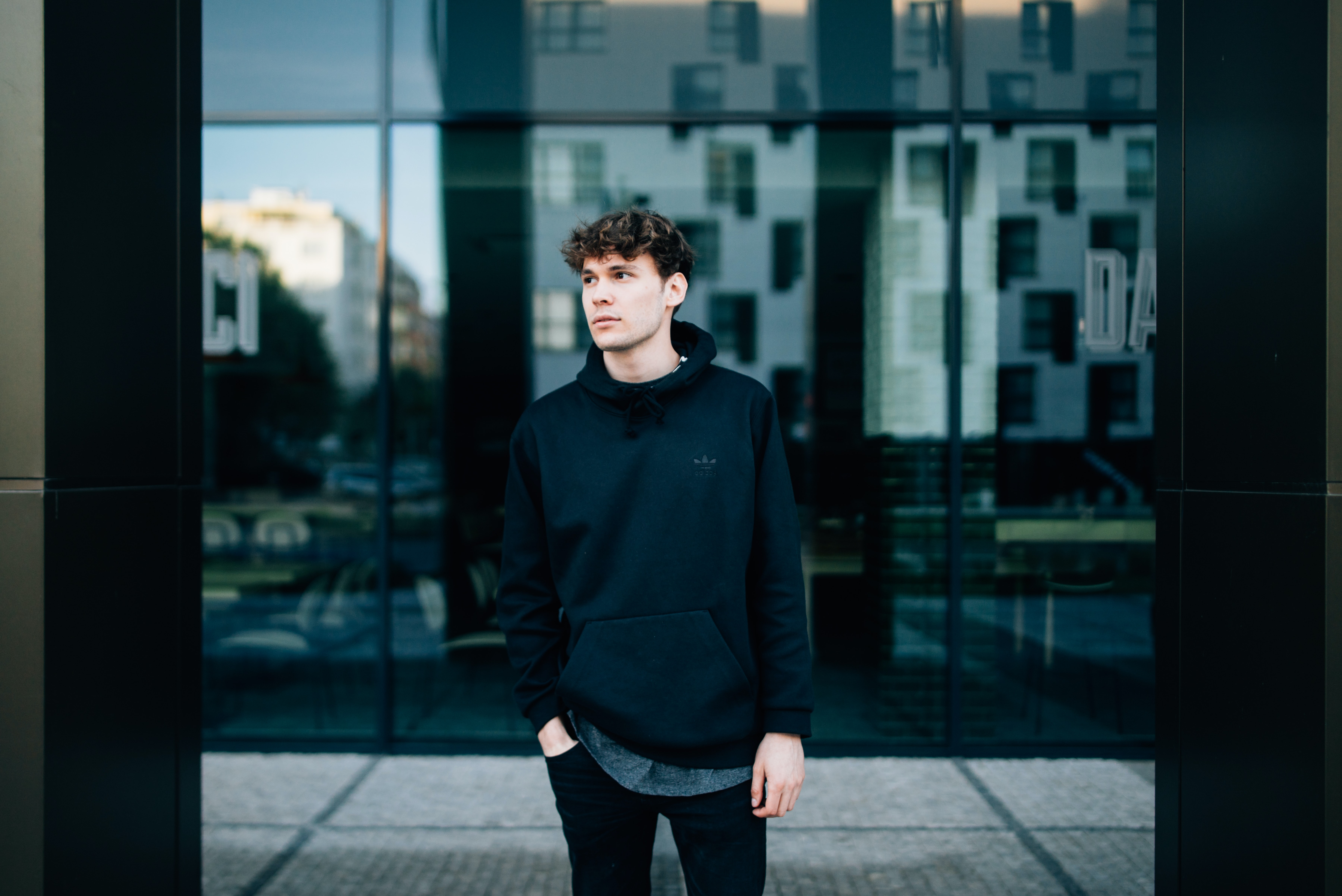 Man in a balck hoodie stands in front of a reflective store window