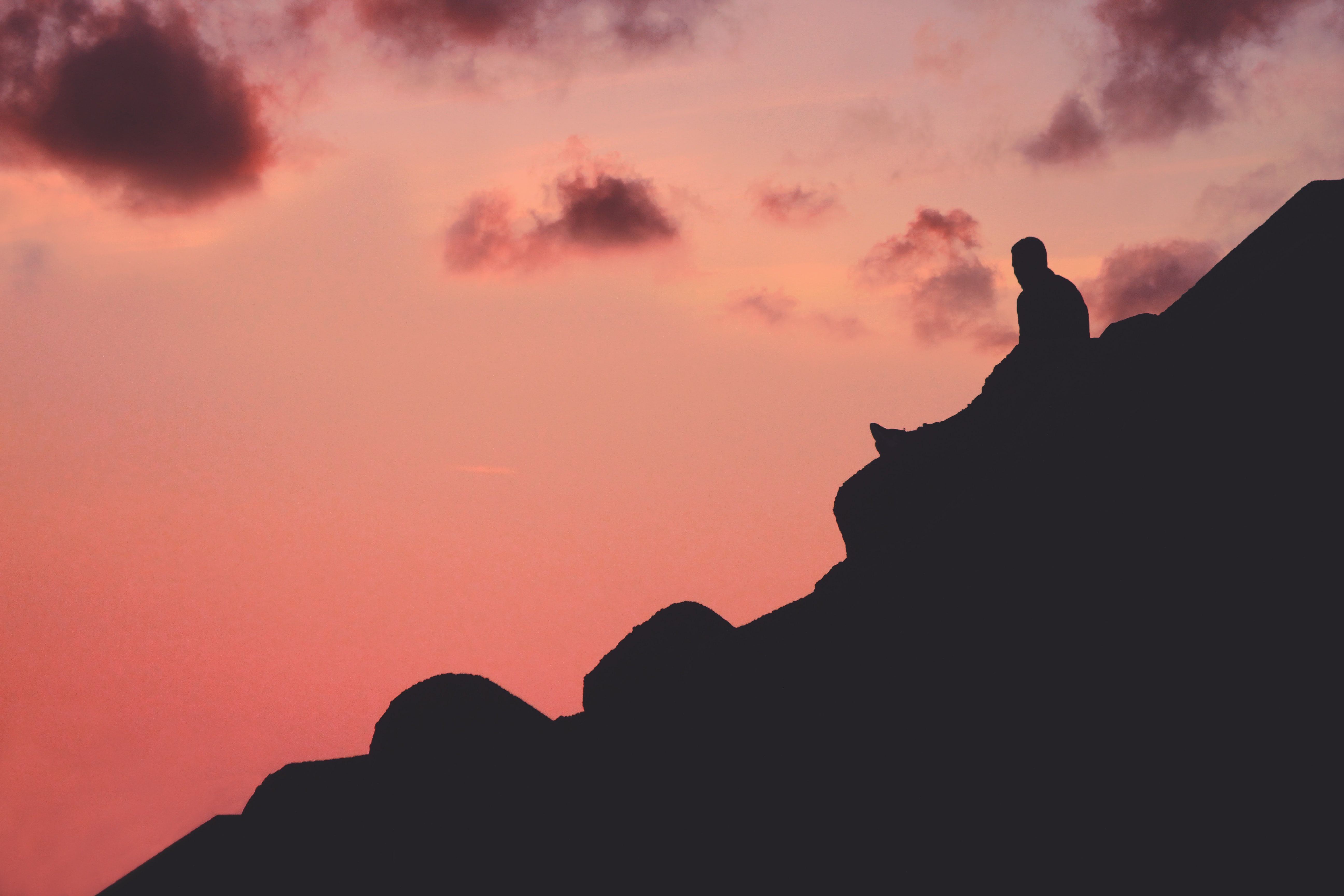 silhouette of man sitting on cliff