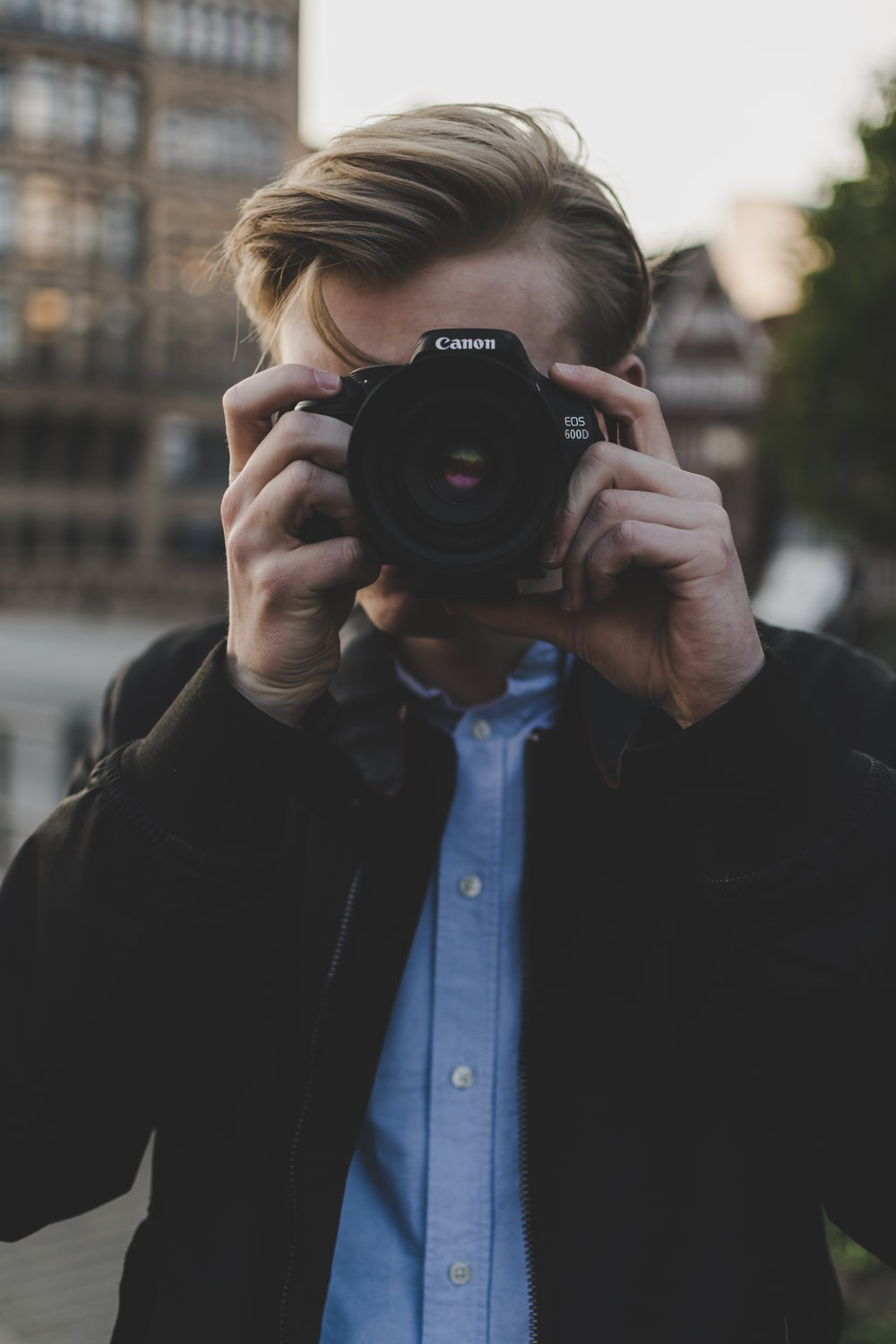 man using black Canon EOS camera during day time